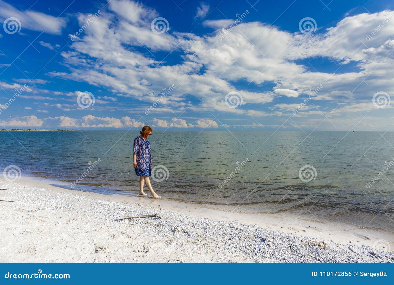 Moça dentro no vestido azul que anda na praia do lago