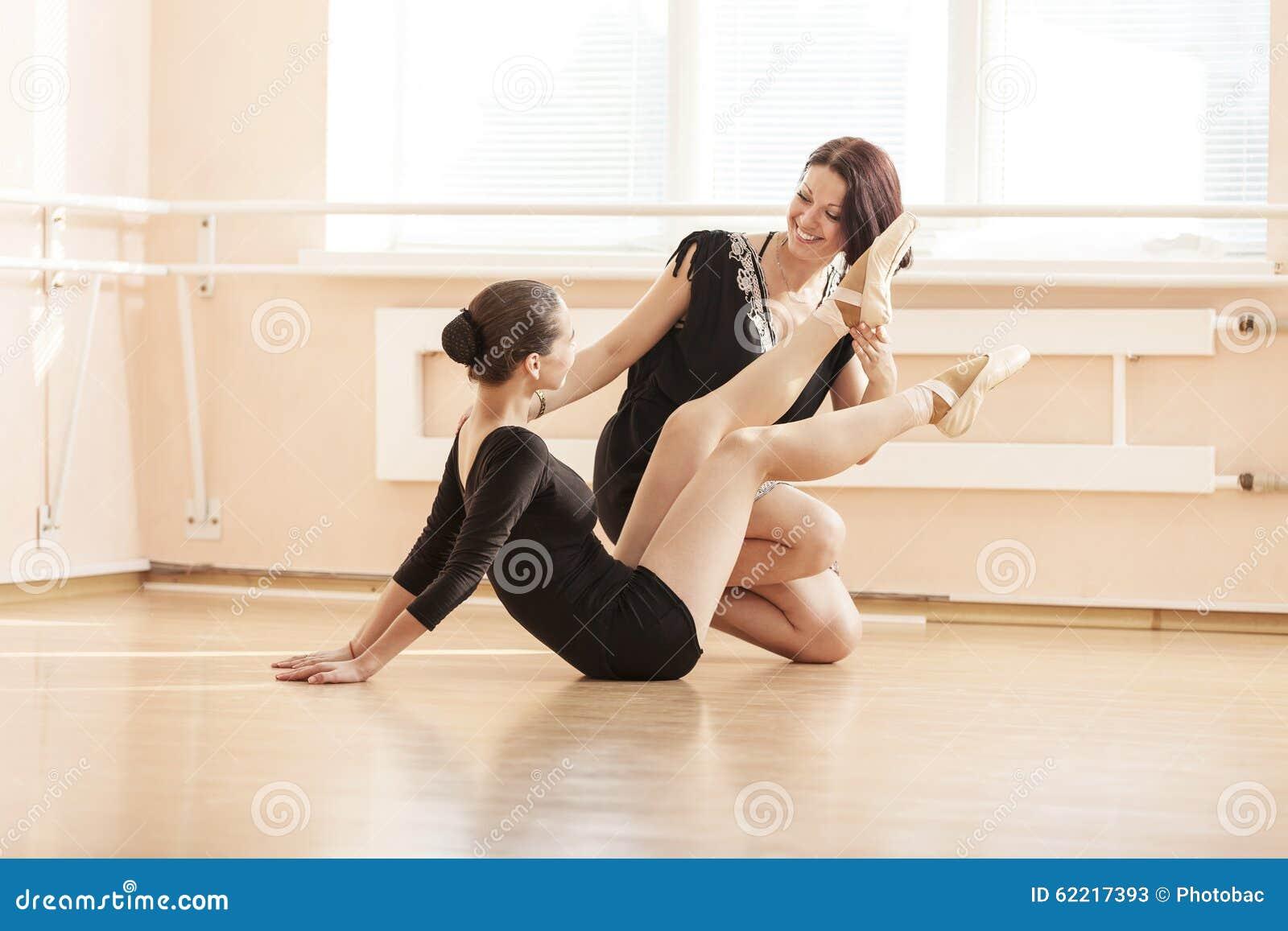A moça do professor do bailado mostrando como executar o exercício no assoalho