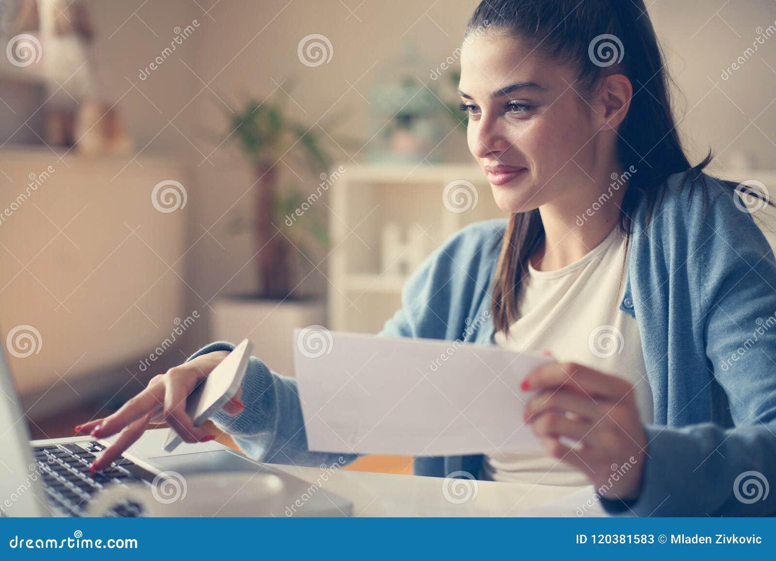 Moça em casa que guarda o original e que datilografa no portátil