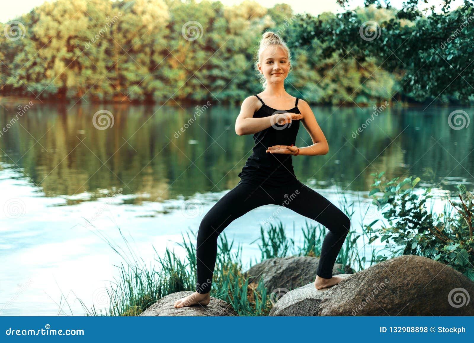 Moça em um t-shirt preto e nas caneleiras que fazem a ioga no lago no parque