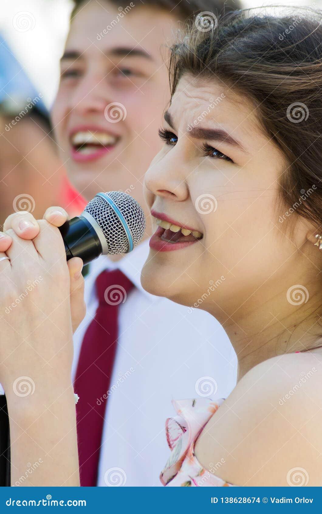 Moça em uma competição do karaoke em um parque da cidade Close-up