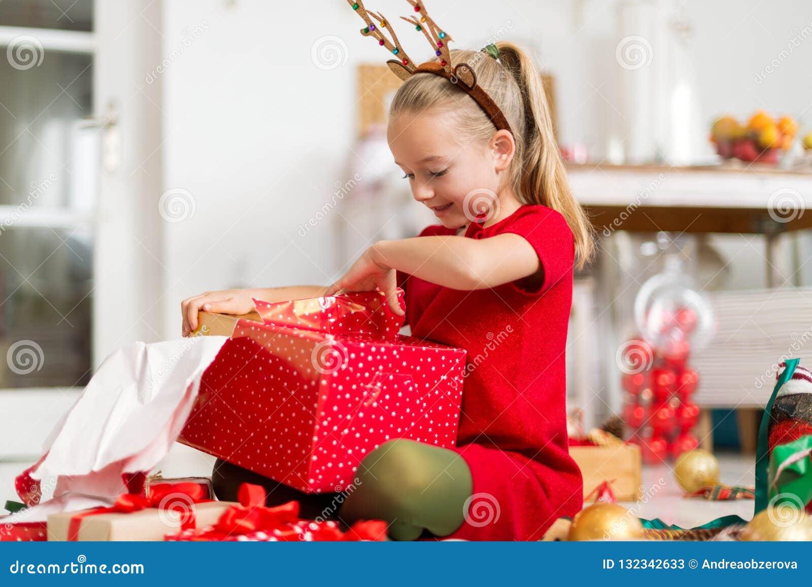 Moça entusiasmado super bonito que abre o grande presente de Natal vermelho ao sentar-se no assoalho da sala de visitas Tempo cân