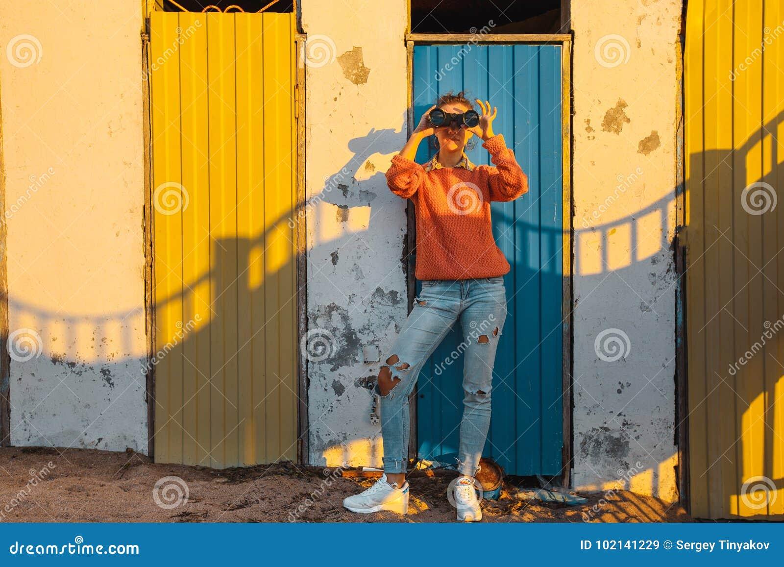 A moça está perto de uma parede colorida e olha através dos binóculos