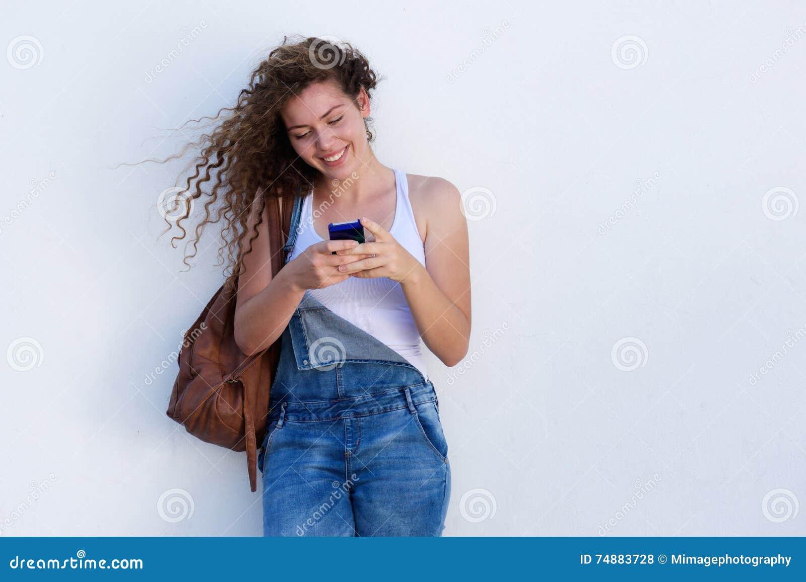 Moça feliz em texting do telefone celular