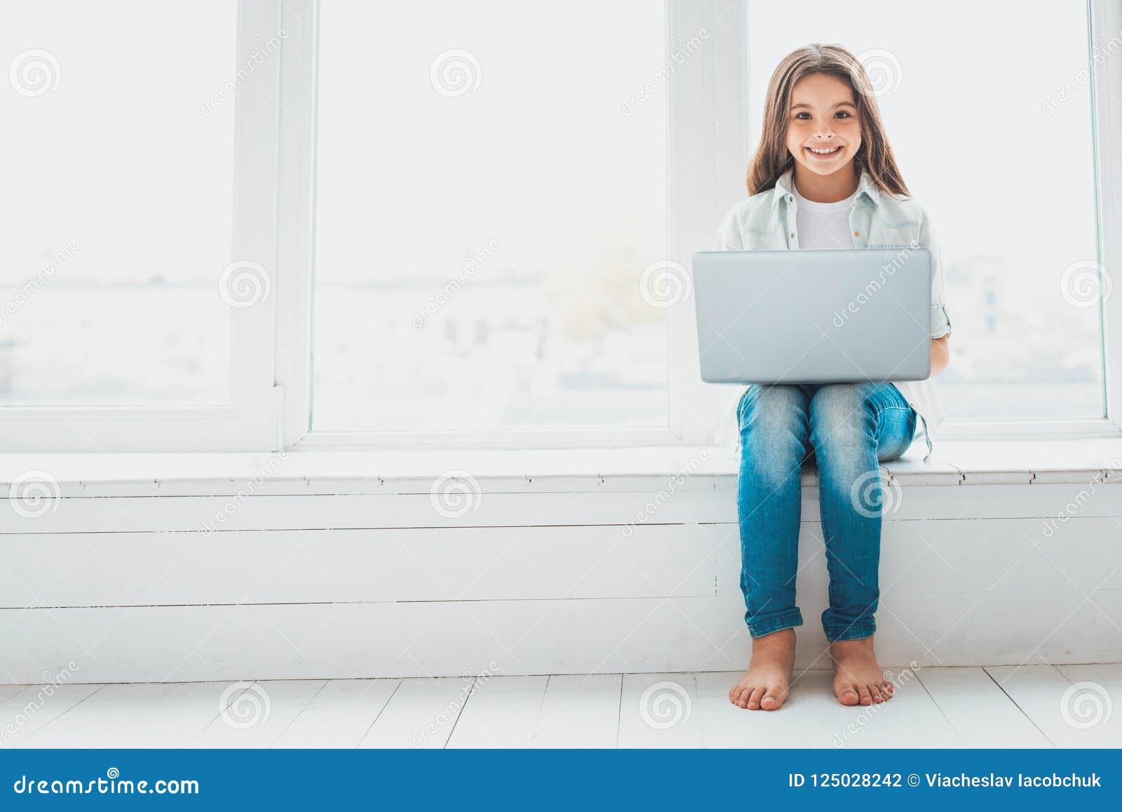Moça moderna que sorri ao conversar através do Internet com amigos