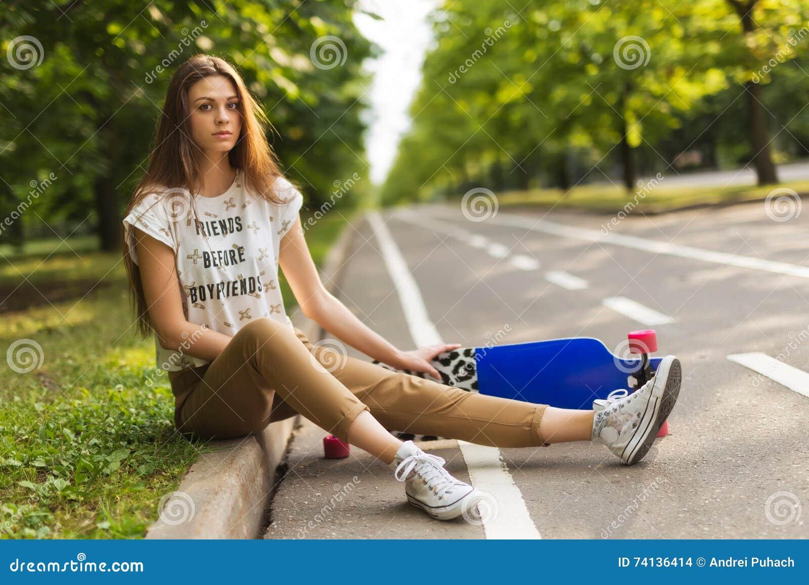 A moça muito bonita com o cabelo longo que senta-se no parque na trilha e mantém o lorgbord skateboarding lifestyle