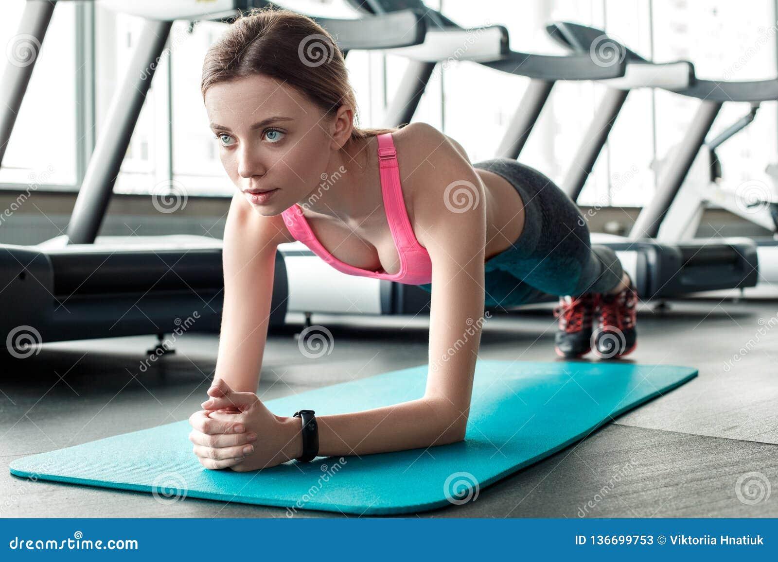 Moça na posição saudável do estilo de vida do gym na pose da prancha no close-up concentrado esteira