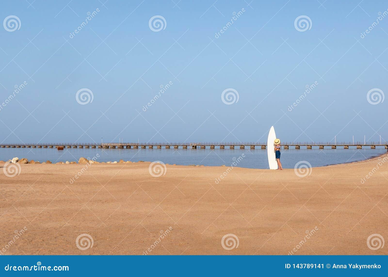 Moça na praia com uma prancha, chapéu no fundo de um cais longo