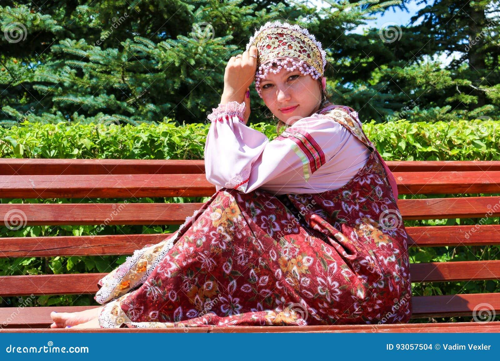 A moça no traje popular do russo senta-se no banco
