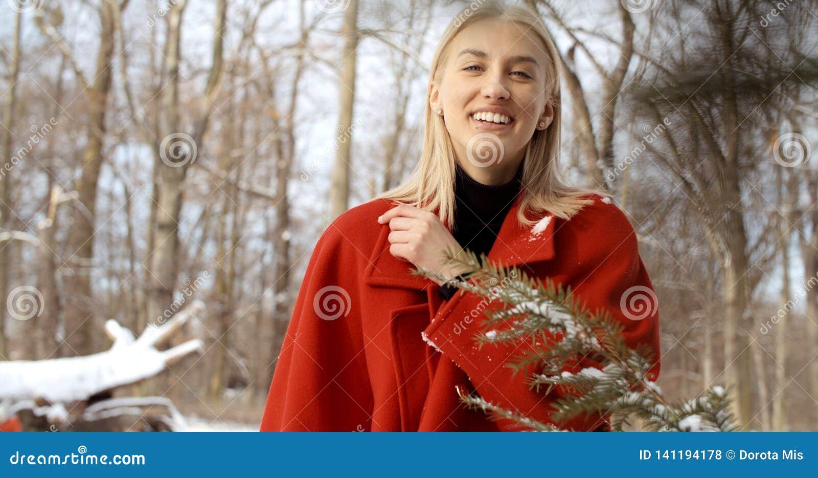 Moça pensativa que aprecia o inverno em um parque da cidade
