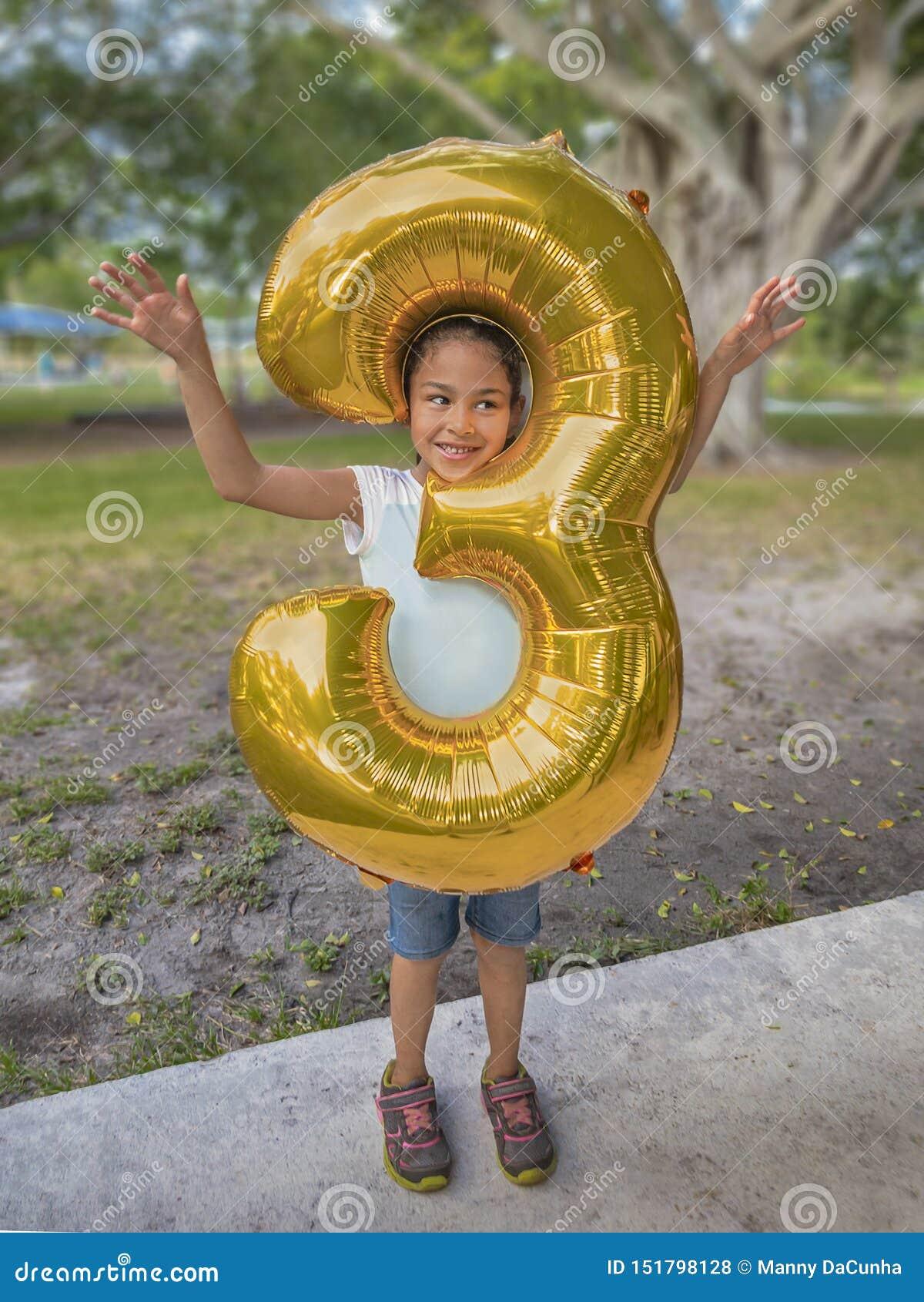 A moça pica sua cabeça através de um balão metálico do ouro do grande número três