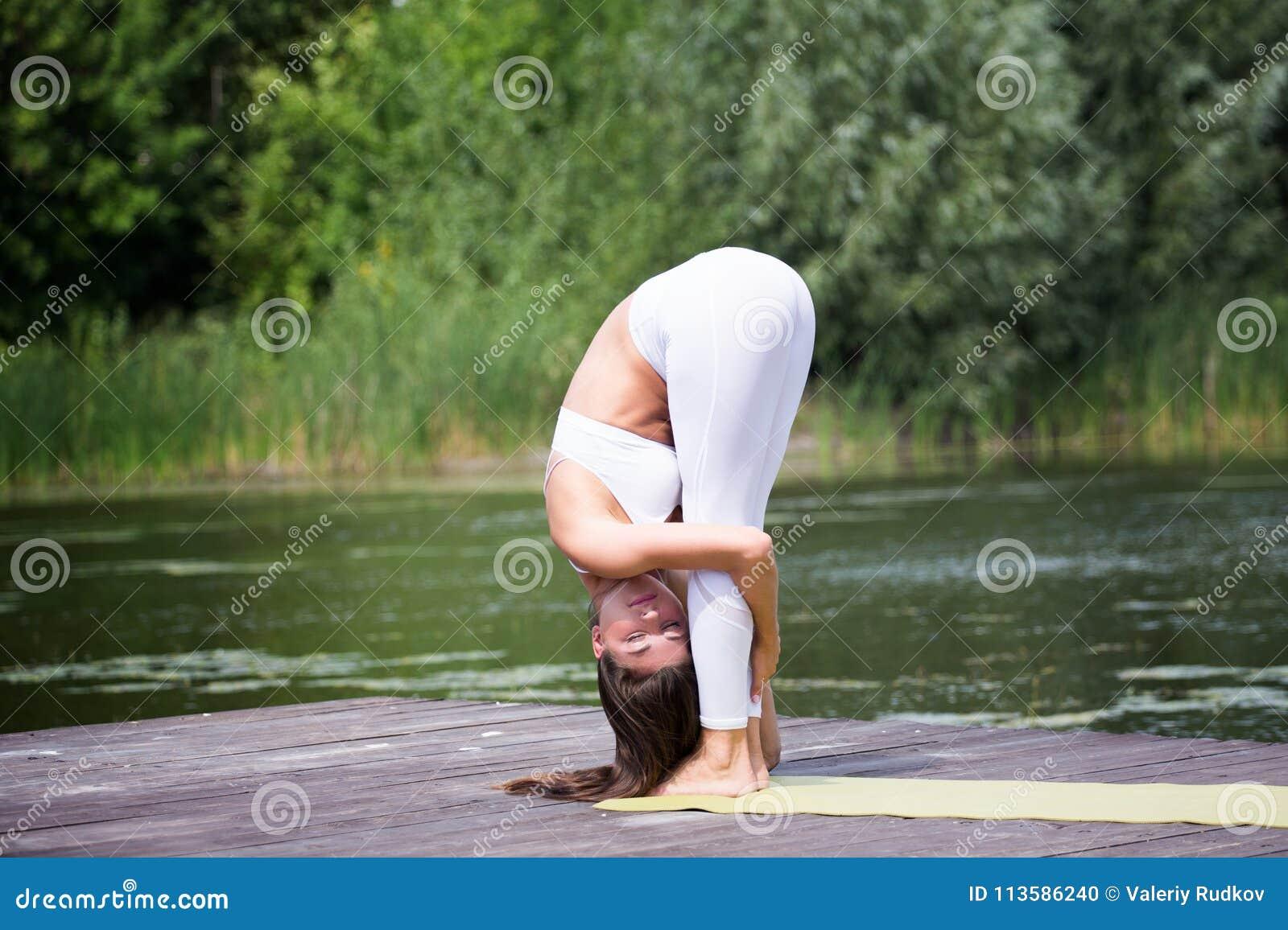 A moça pratica a ioga na costa do lago, o conceito de apreciar a privacidade e a concentração, luz solar
