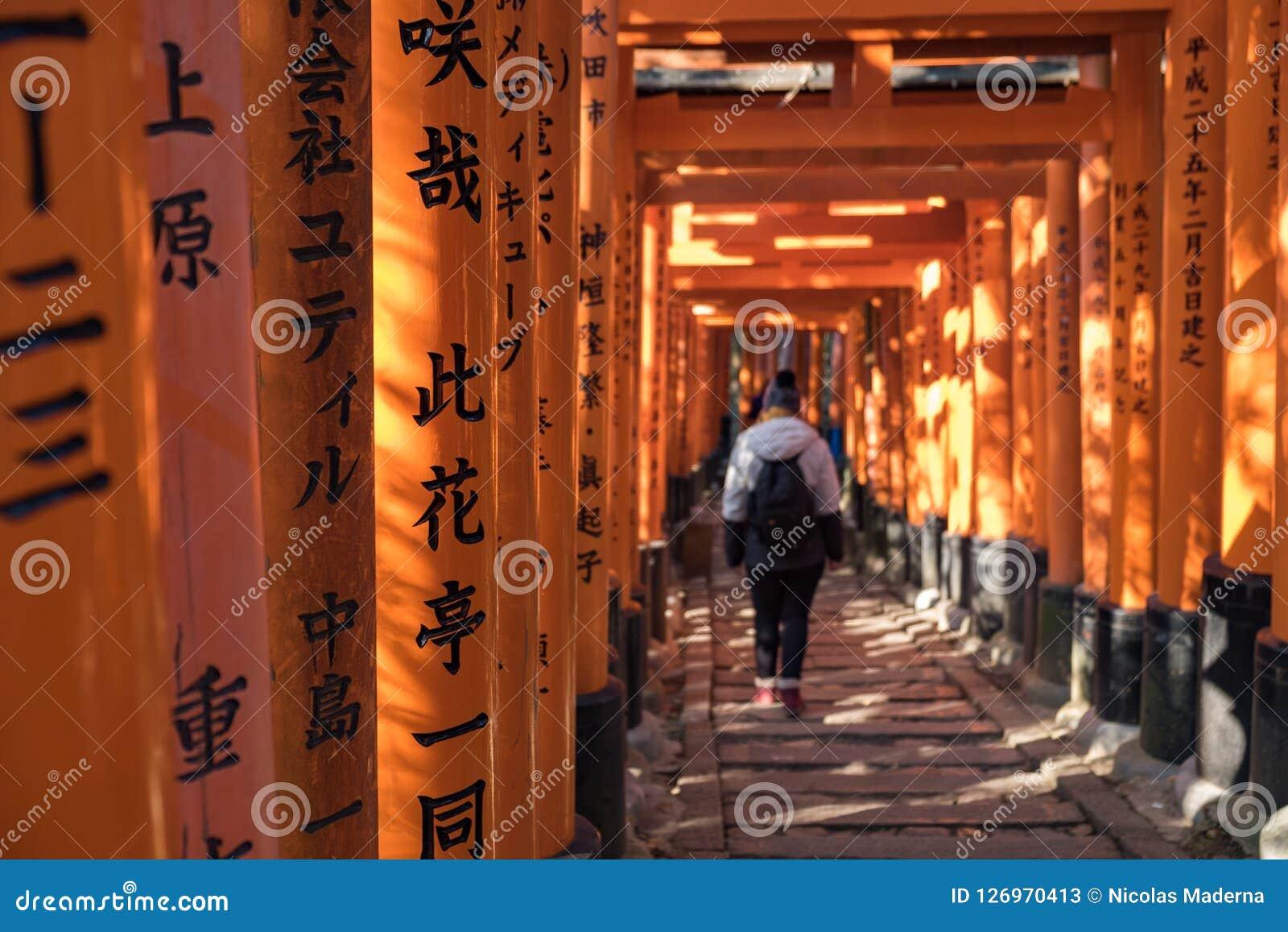 Moça que anda abaixo de um trajeto completamente de toriis de madeira vermelhos com inscrição pretas em Fushimi Inari Shri