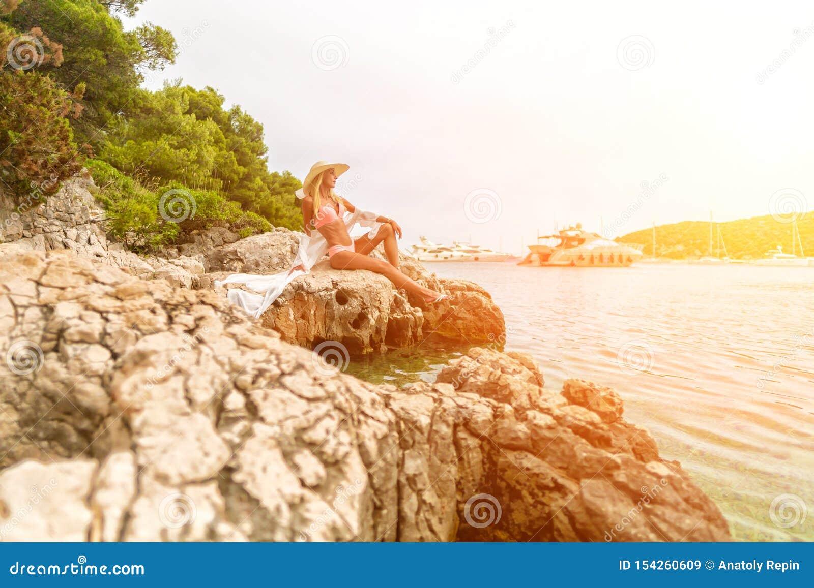 Moça que senta-se nas rochas apenas e que olha o mar