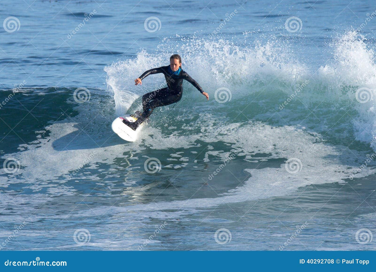 Moça que surfa uma onda em Califórnia