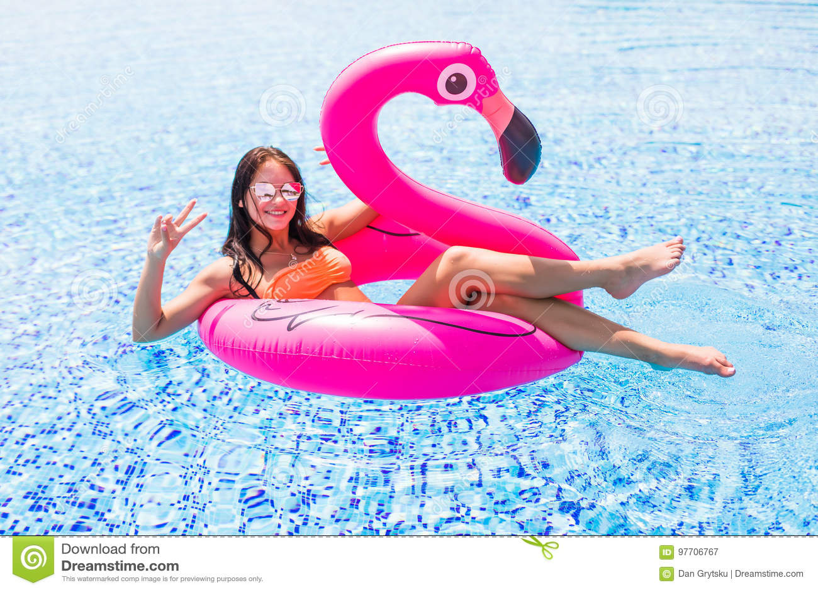 Moça que tem o divertimento e que ri em um colchão cor-de-rosa gigante inflável do flutuador da associação do flamingo em um biqu