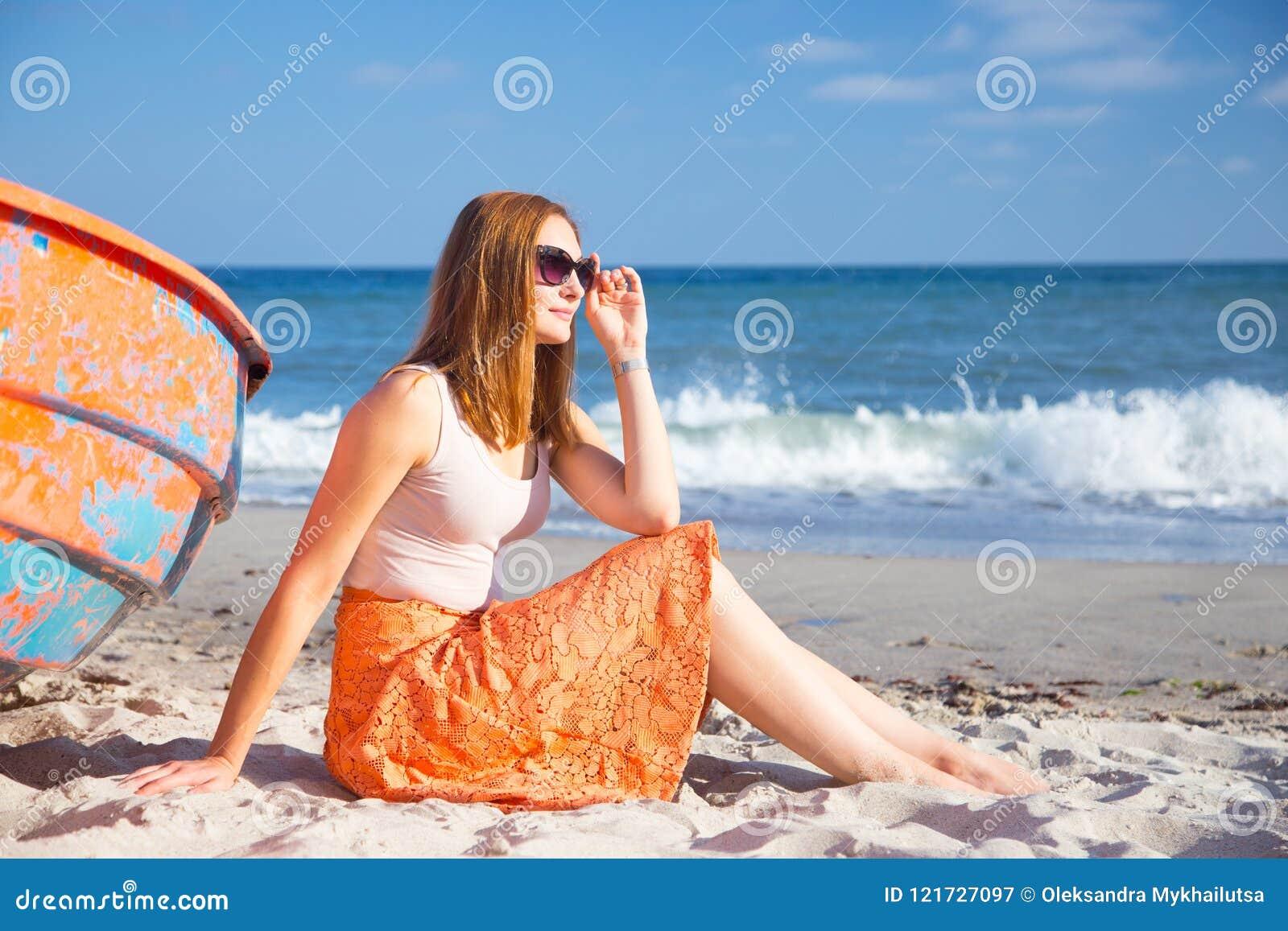 Moça ruivo bonita nos óculos de sol e na saia que relaxam na praia perto do barco alaranjado