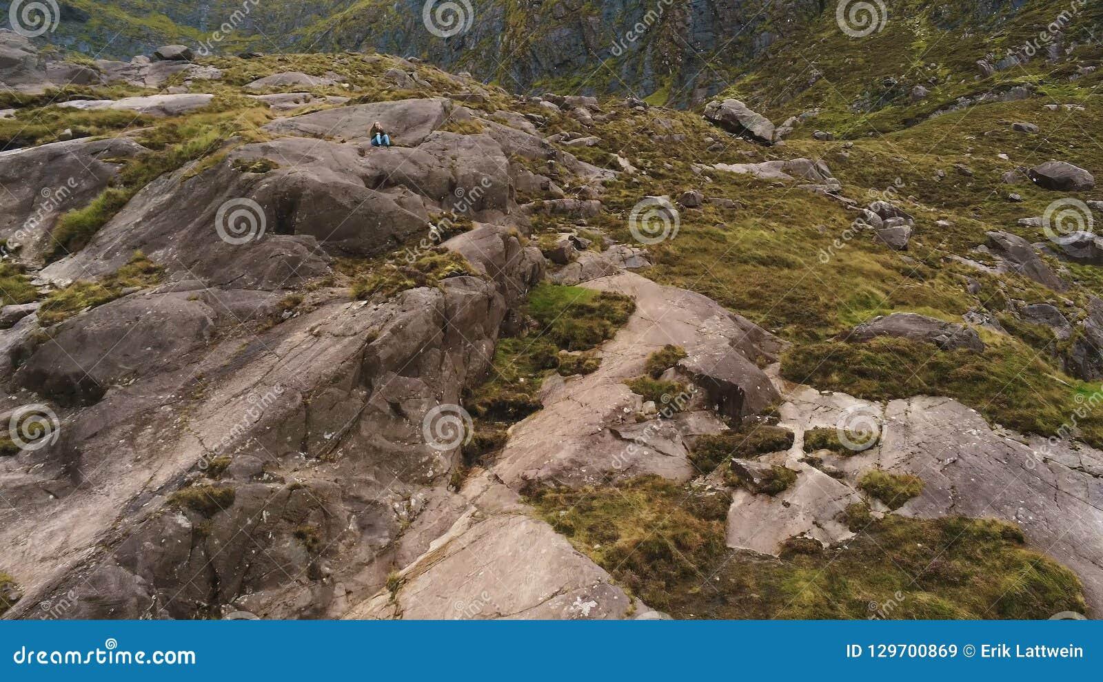 A moça senta-se apenas nas montanhas rochosas da península do Dingle