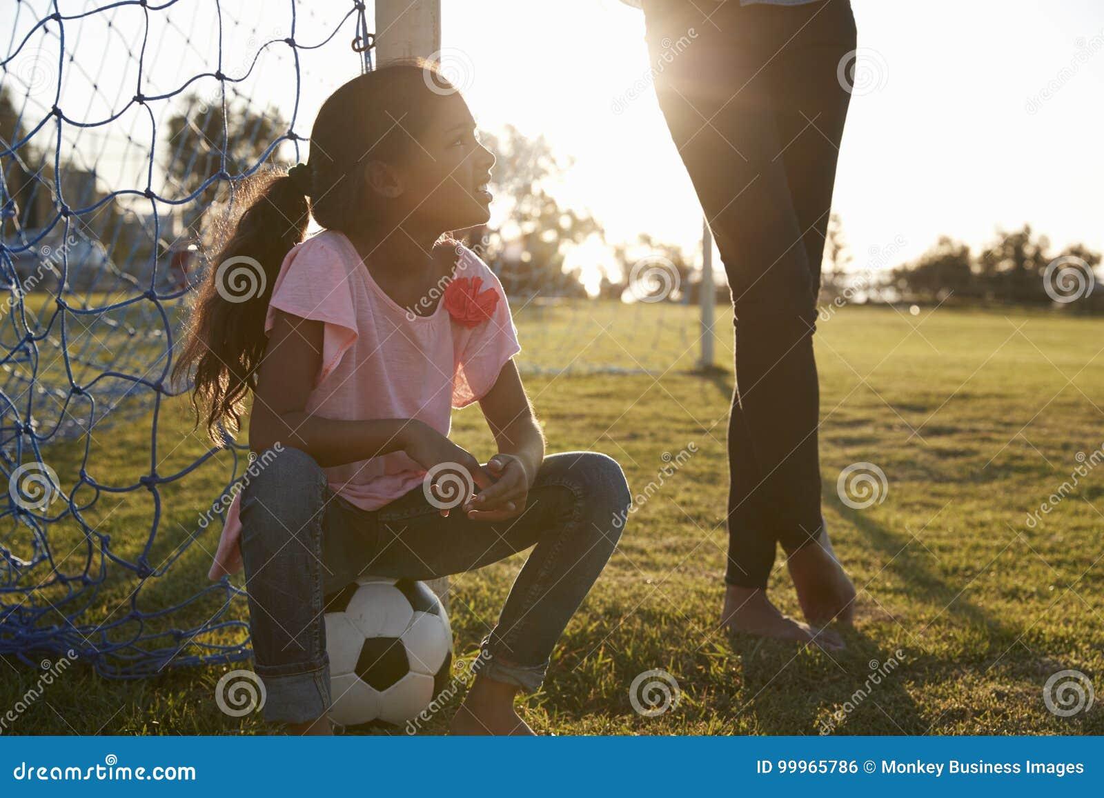 A moça senta-se na bola ao lado de seu mum em um passo de futebol