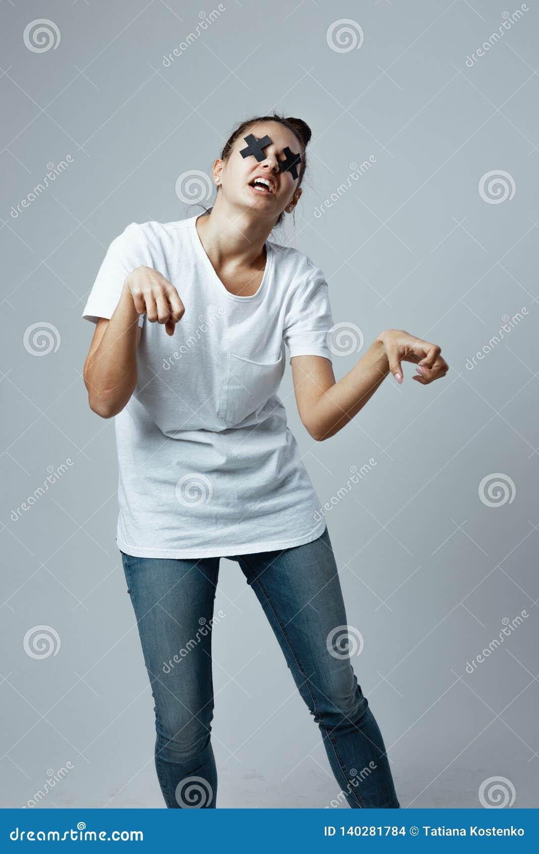 A moça vestida no t-shirt e nas calças de brim brancos com cruzes pretas da fita adesiva nos olhos está no branco