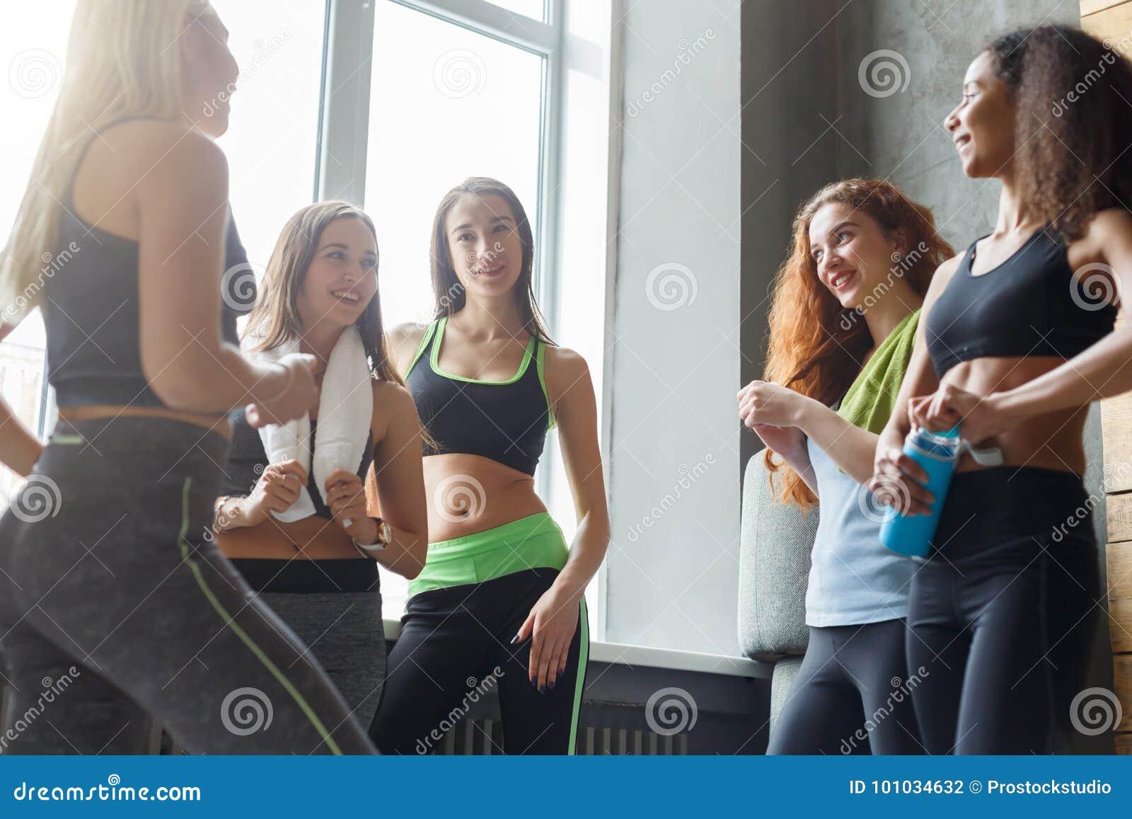 Moças no sportswear que conversam antes da classe de dança