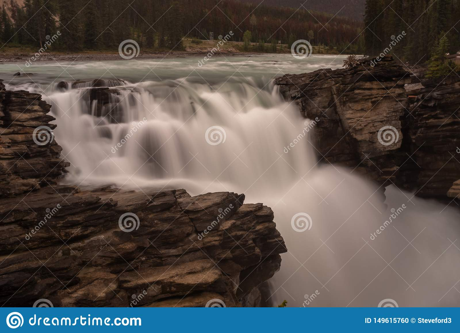 Można Athabasca siklawa w Banff parku narodowym, Kanada potok woda gniesie przez przerwy w skałach i spada dużo