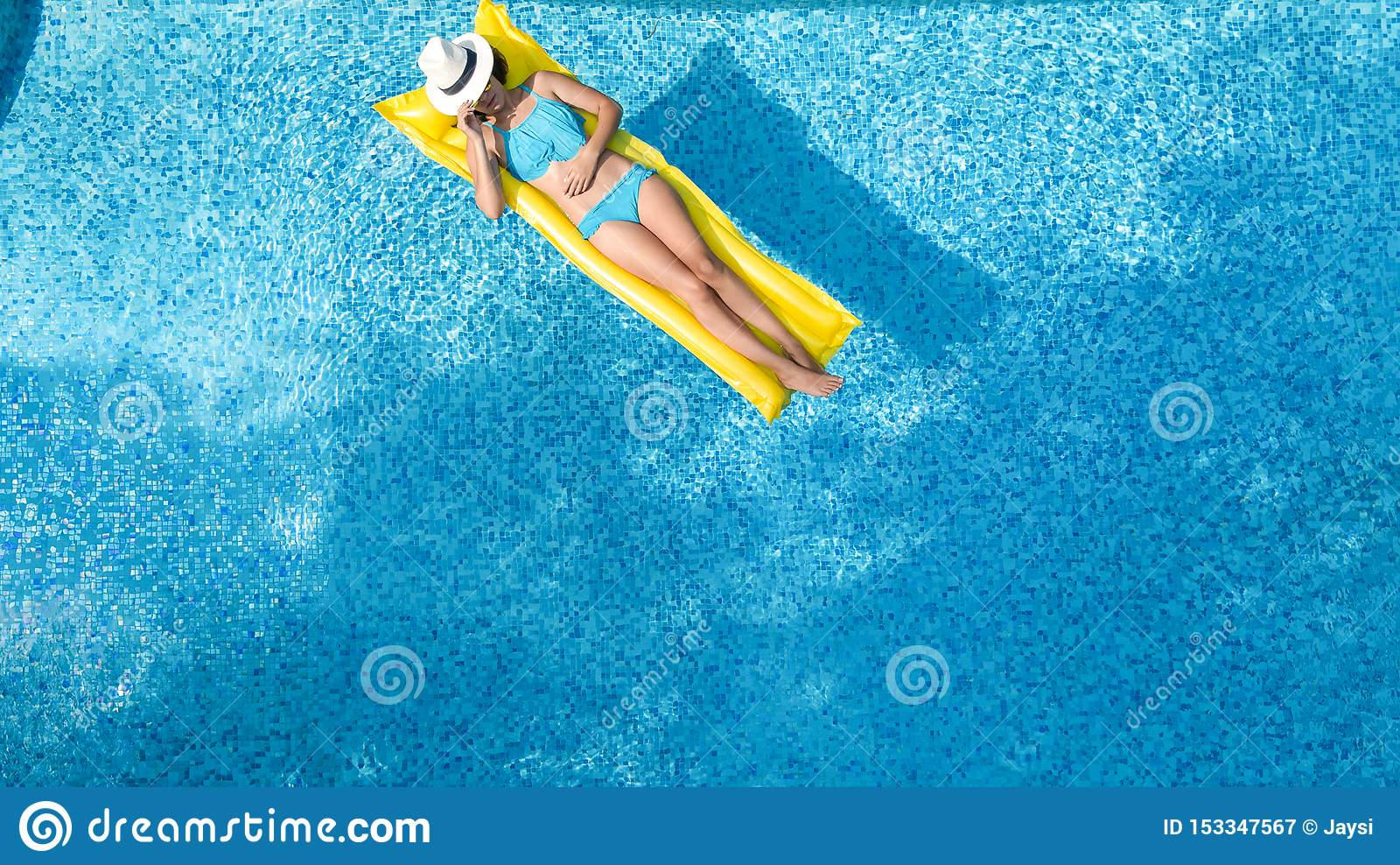 A mo?a bonita que relaxa na piscina, nadadas no colch?o infl?vel e tem o divertimento na ?gua em f?rias em fam?lia