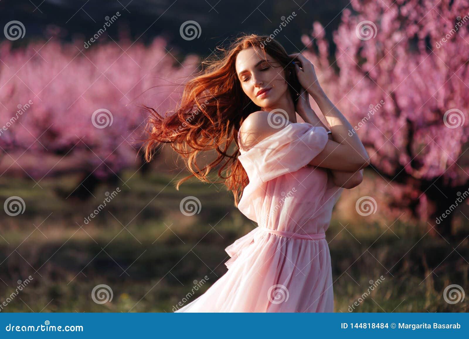 Mo?a bonita sob a ?rvore cor-de-rosa de floresc?ncia