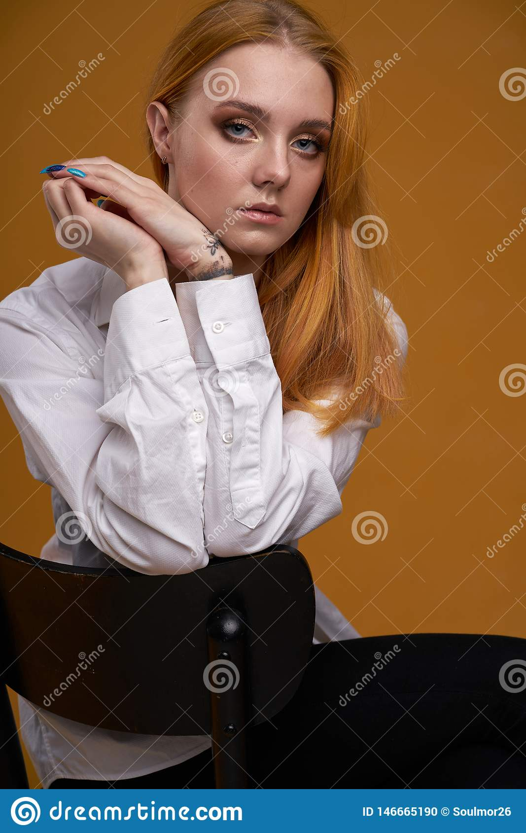 Mo?a ? moda com o cabelo encaracolado, sorrindo cutely, levantando, no fundo amarelo