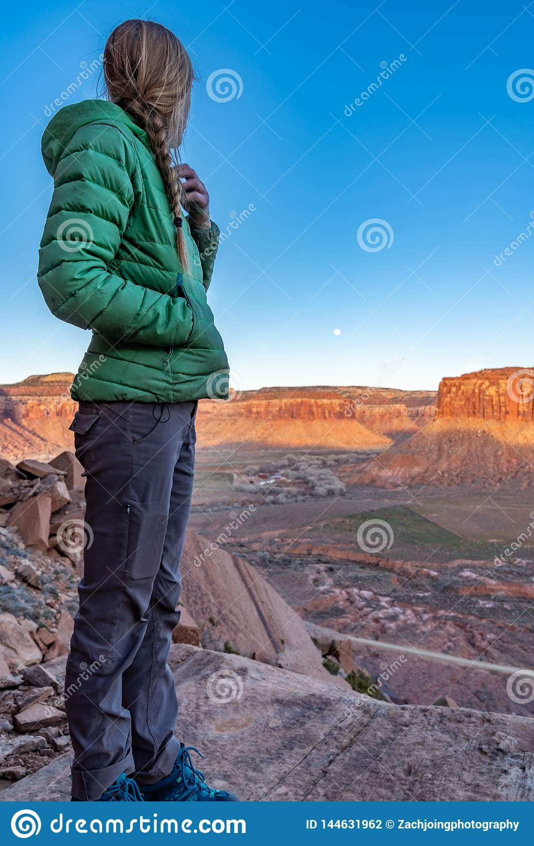 3/21/19 Moab, Utah. Woman watching the moon rise and the sun set, after a long day of rock climbing.