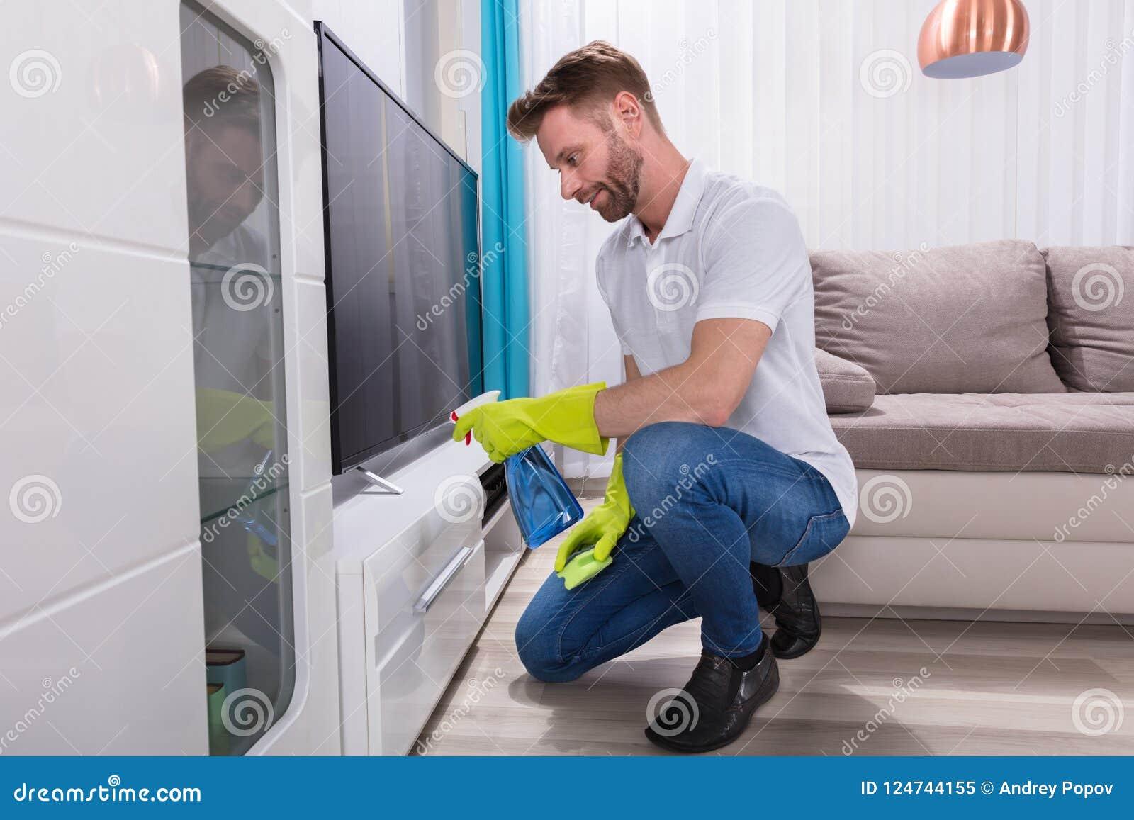Mobília da limpeza do homem com garrafa do pulverizador