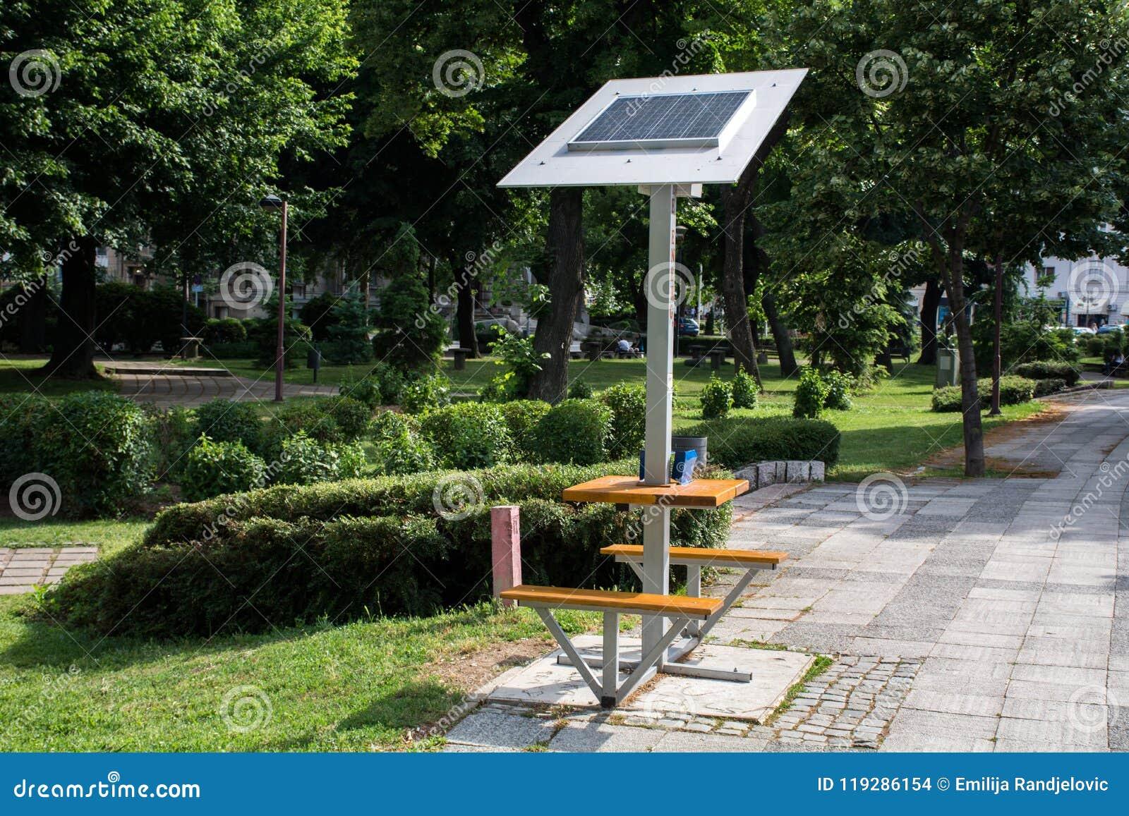 Mobiel zonnepaneel op de bank in openbaar park voor batterij het laden