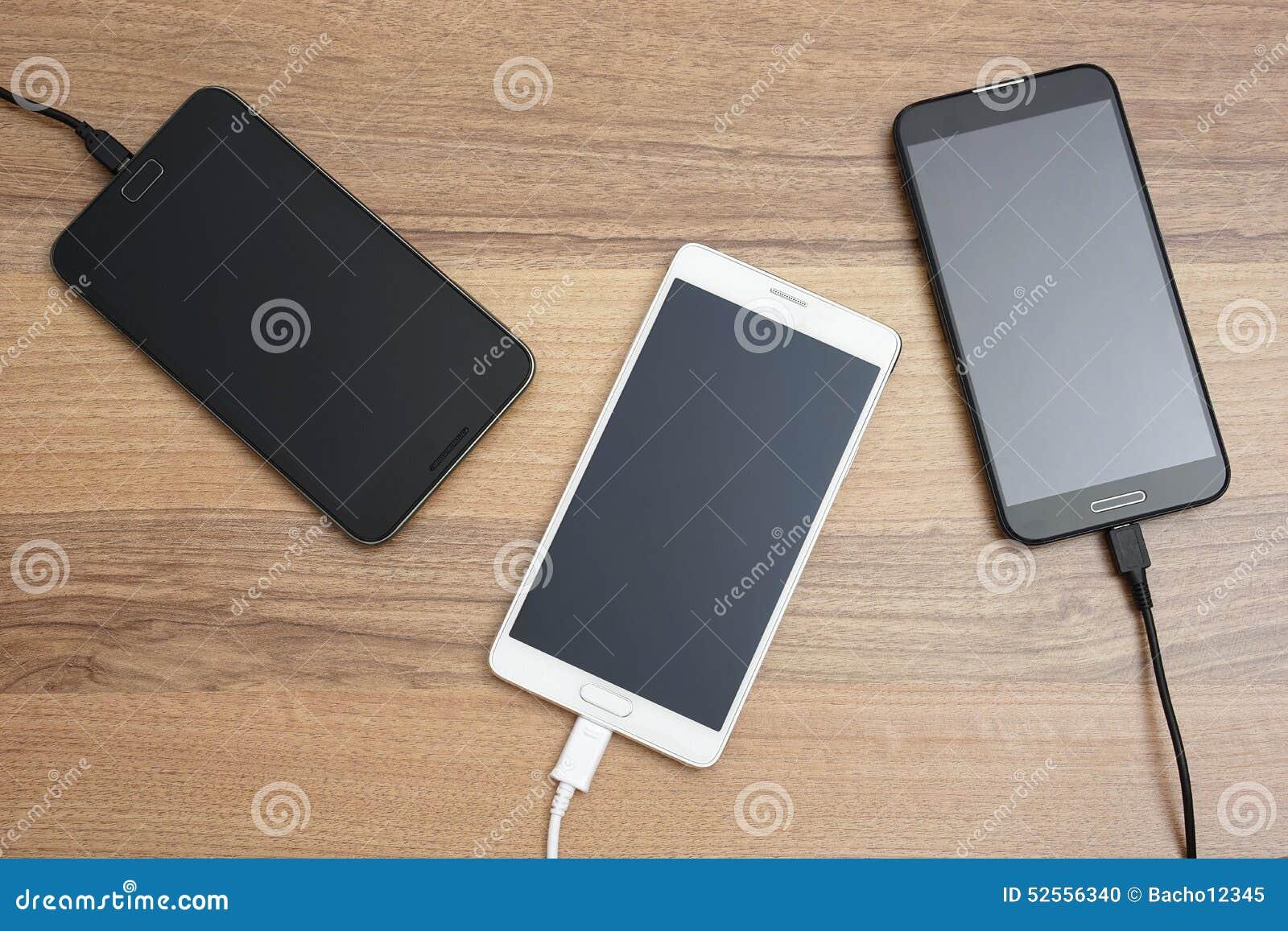 Mobiele slimme telefoons die op houten bureau laden
