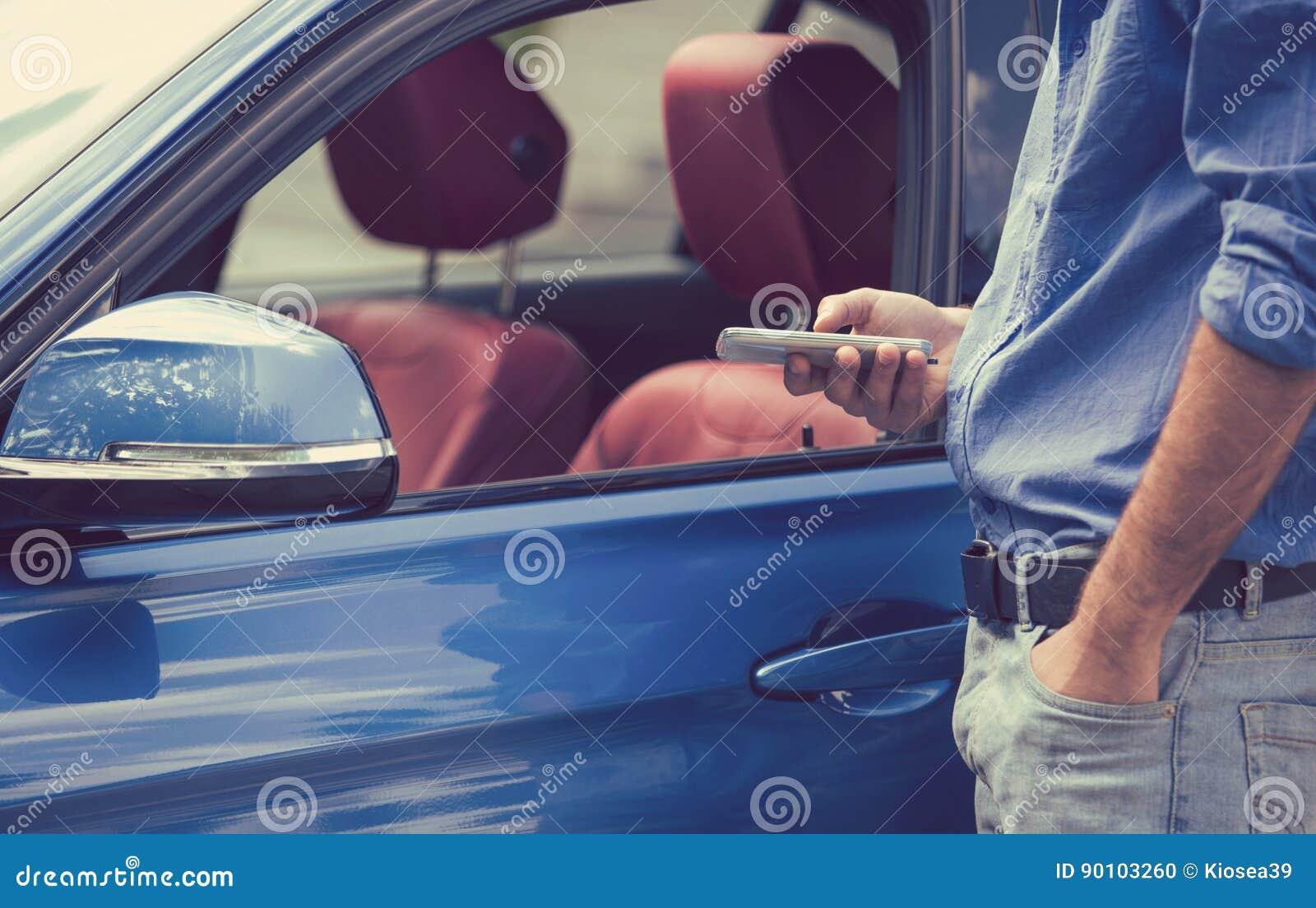 Mobiele telefoon apps voor voertuigeigenaars Mens die slimme telefoon met behulp van om zijn auto te controleren