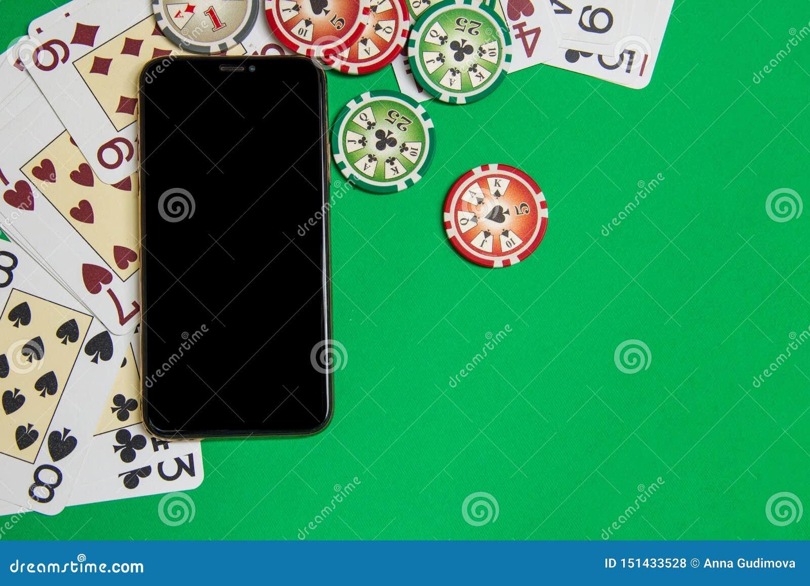 Mobiele telefoon en pookspaanders met speelkaarten op een groene lijst Online casinoconcept