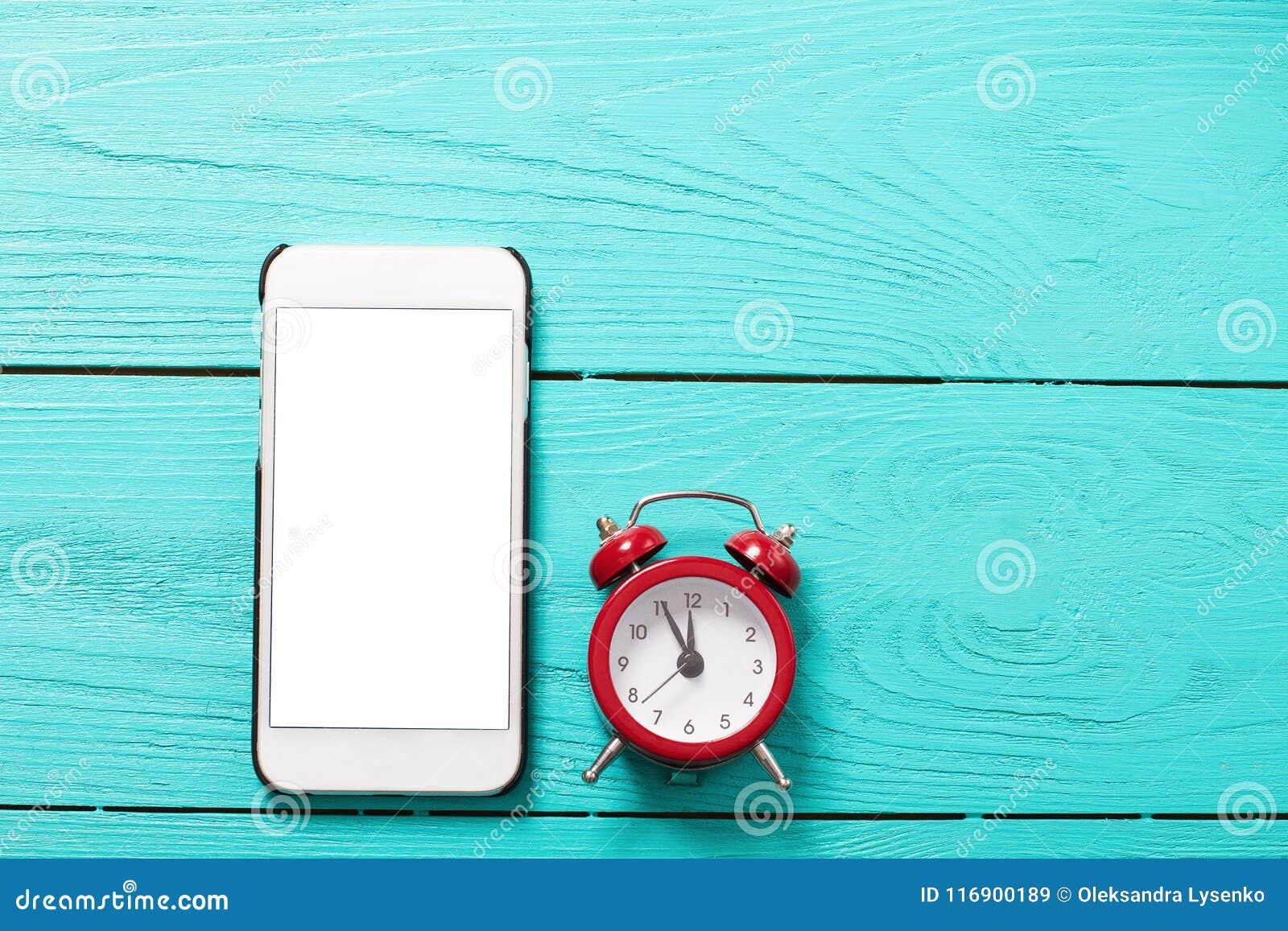 Mobiele telefoon en rode retro wekker met vijf minuten aan de klok van twaalf o ` op blauwe houten achtergrond Hoogste mening en
