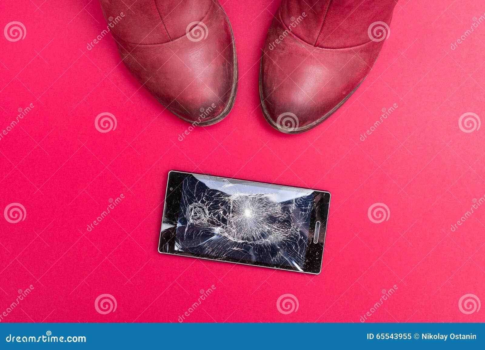 Mobile phone with broken screen on floor