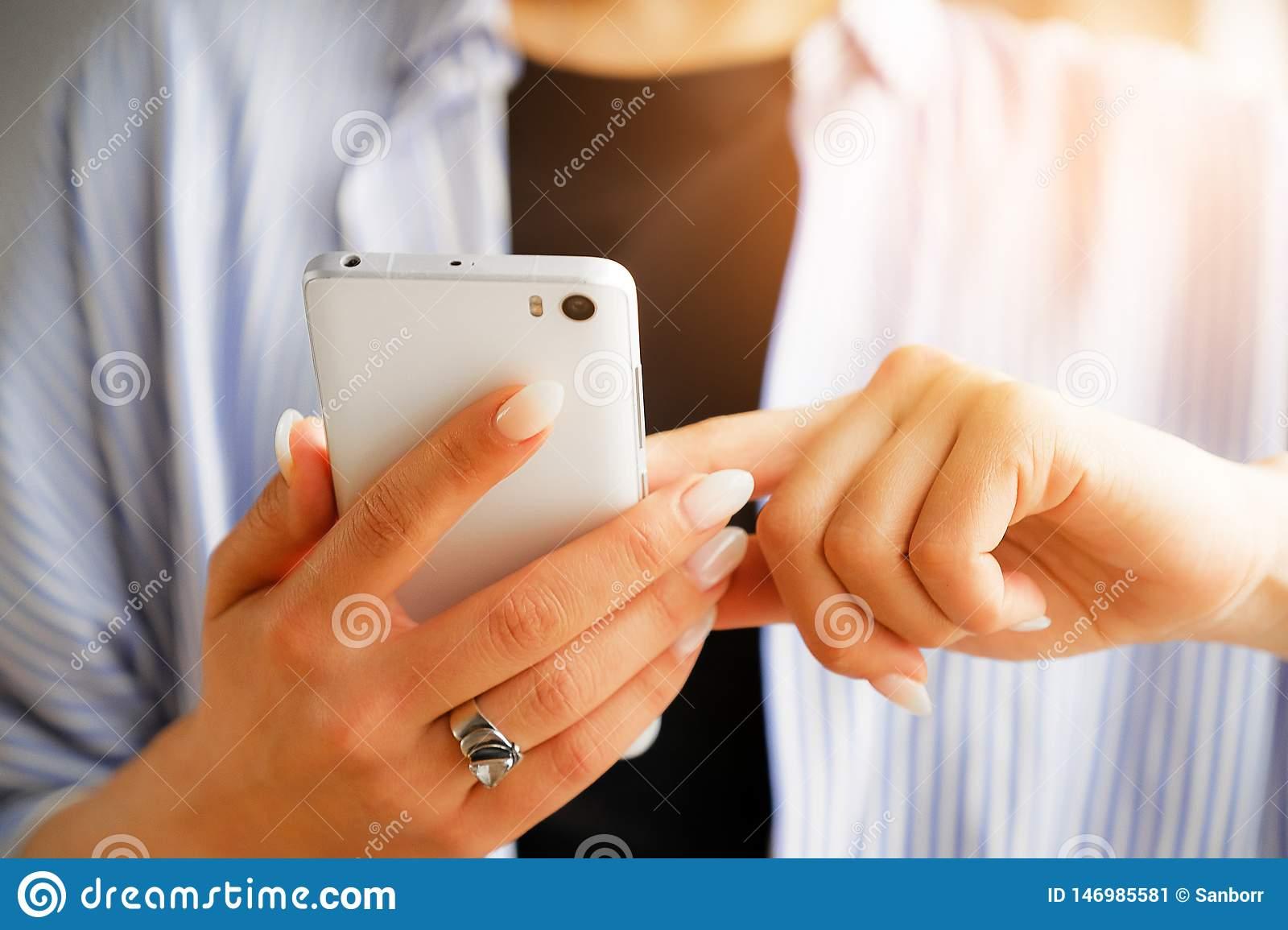 Mobile phone in the hands of a stylish fashion girl freelancer. A young woman in a black t-shirt and striped shirt, with a
