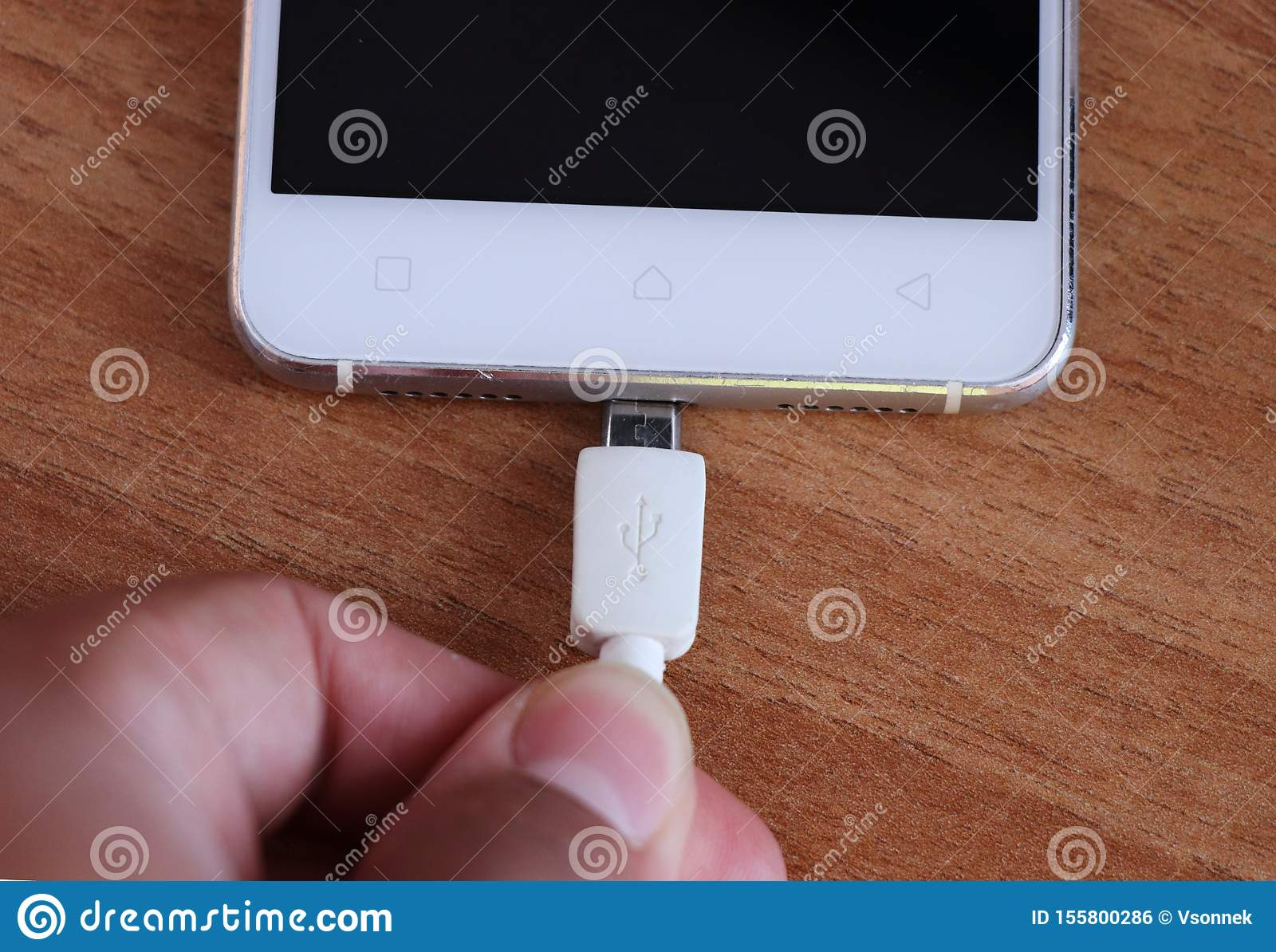 Mobile phone and his charger and person hand. Young hand tries get to charge white phone. Smartphone lies on wooden table. Energy