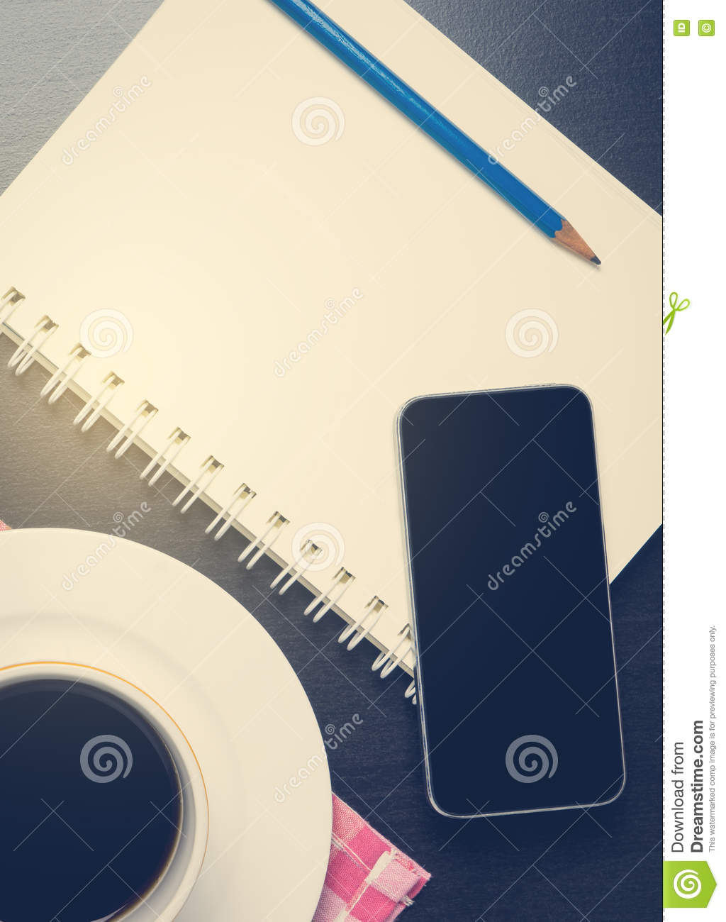 Mobile phone on Notebook with black hot coffee
