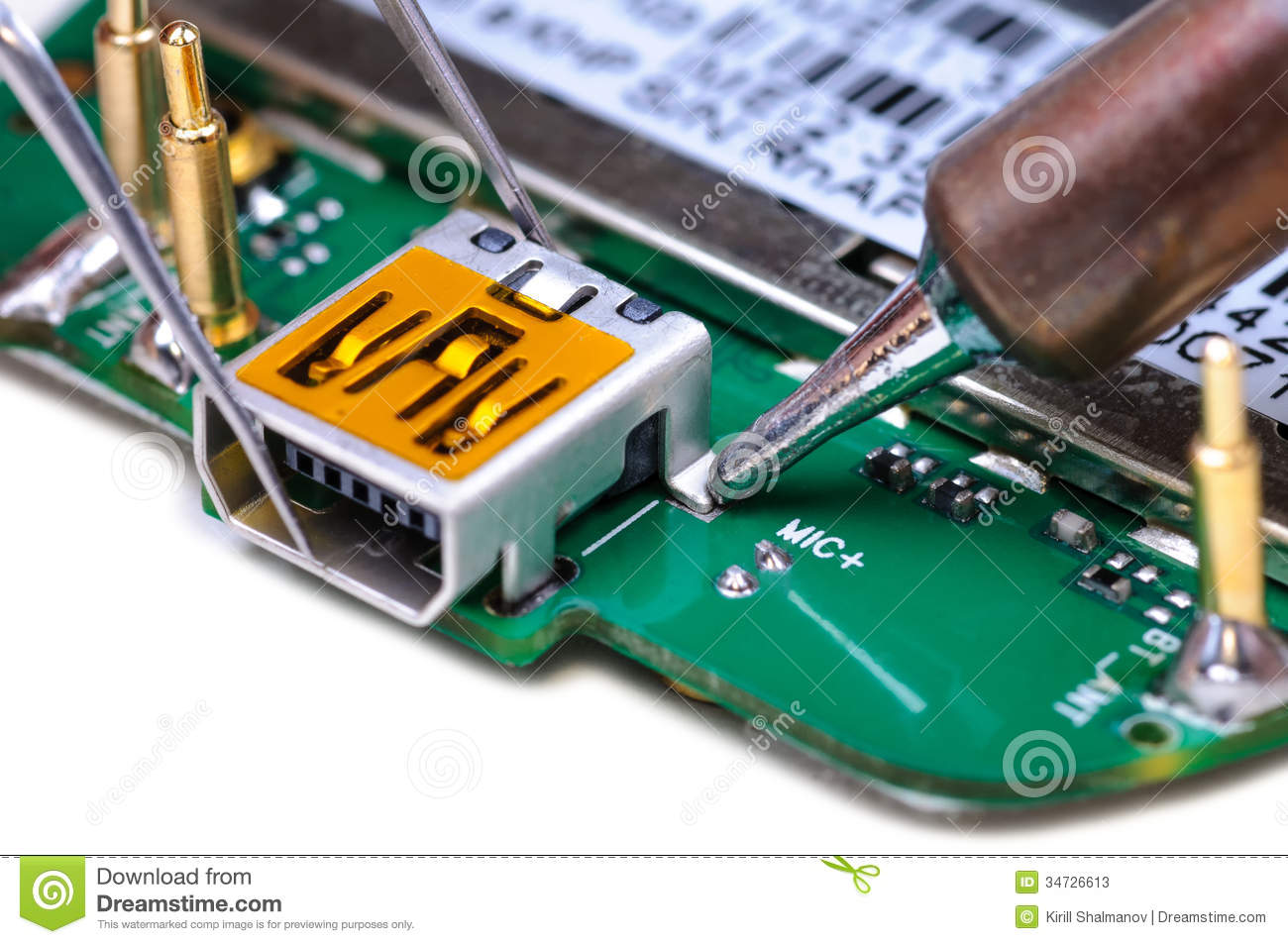 mobile phone repair in electronic lab working place stock imageelectronic technician repairs mini usb socket on mobile phone circuit board close up with selective focus and shallow depth of field