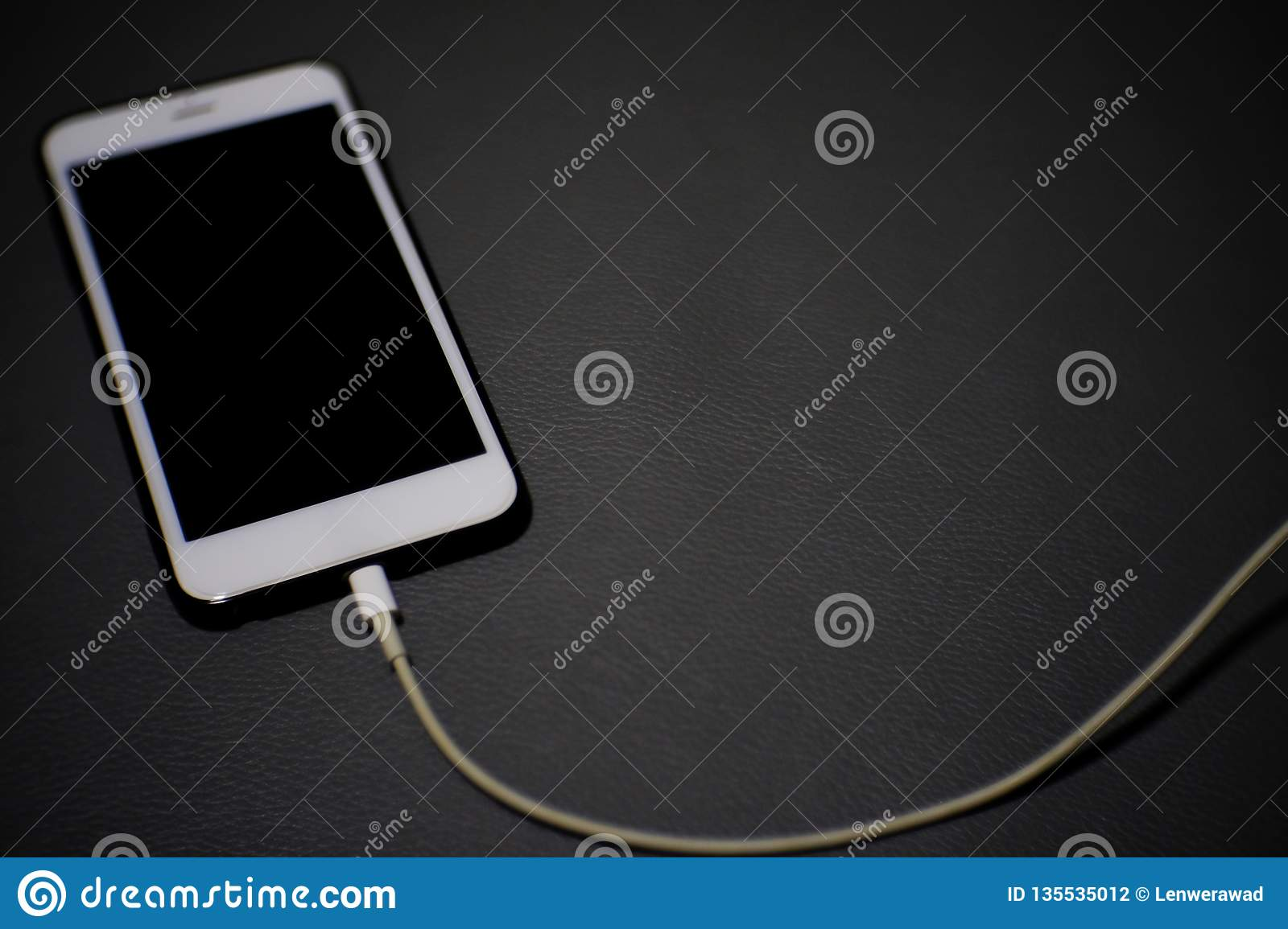mobile smartphone is charging the battery on gray background.
