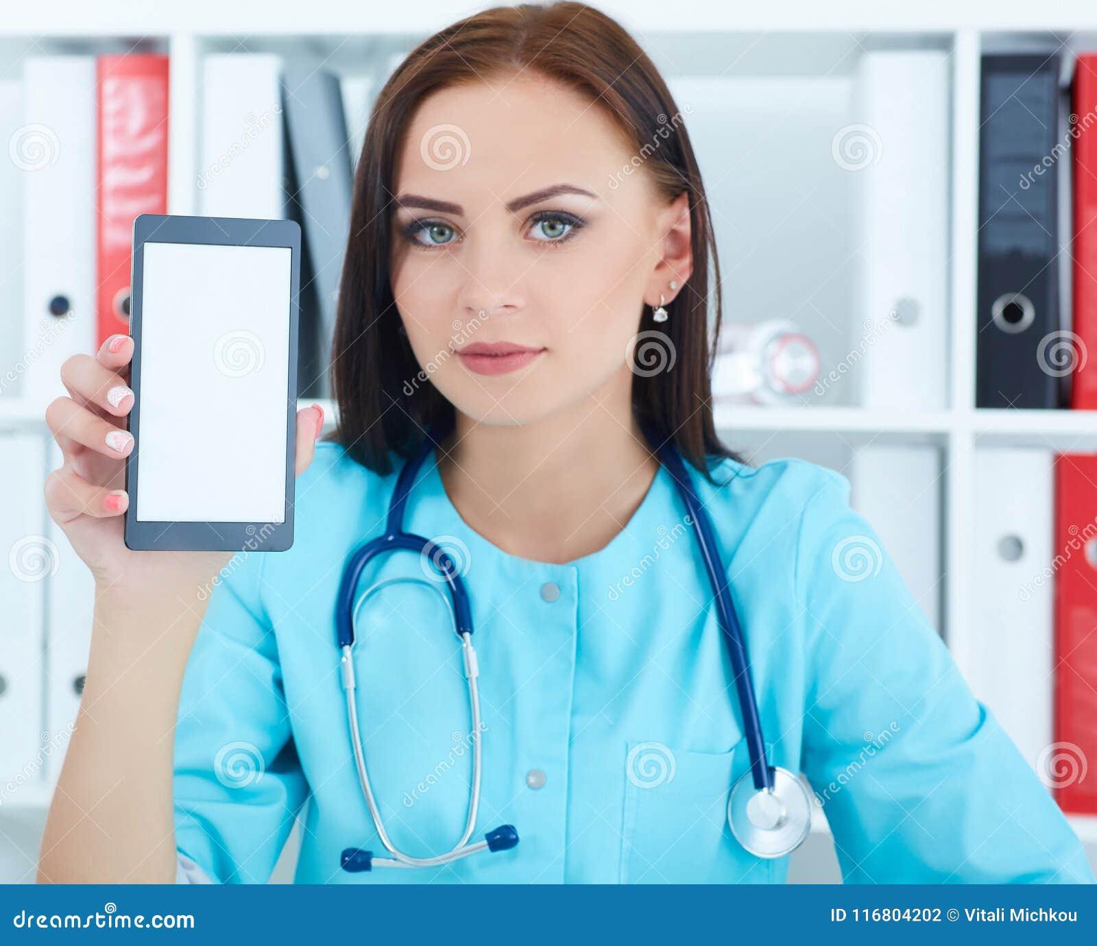 Mobiltelefon och visning för kvinnlig medicindoktor hållande det till kameran Medicinsk utrustning, modern teknologi och