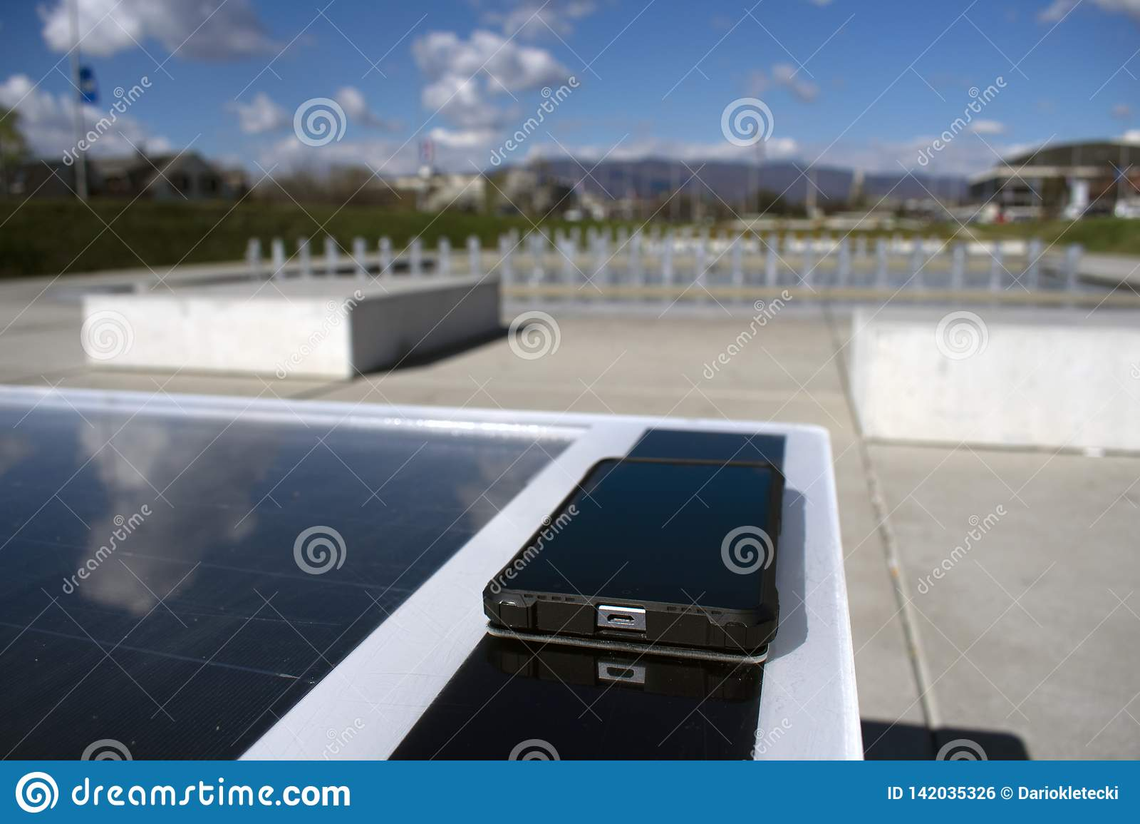 Mobiltelefon som avlägset laddar på en sol- bänk