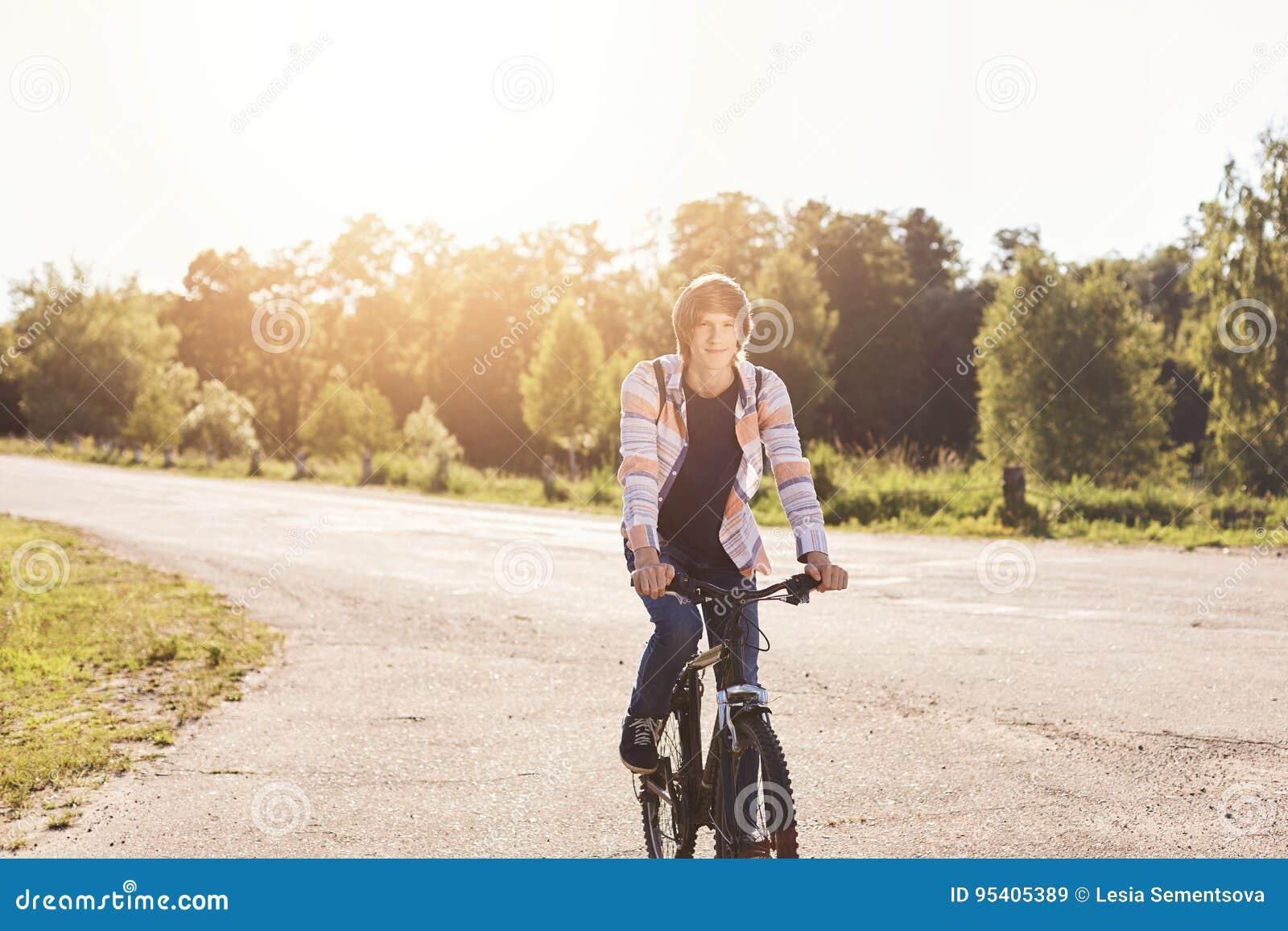 Mochila que lleva de la camisa del adolescente que lleva lindo que monta su bicicleta que tiene resto durante su paseo en el subu
