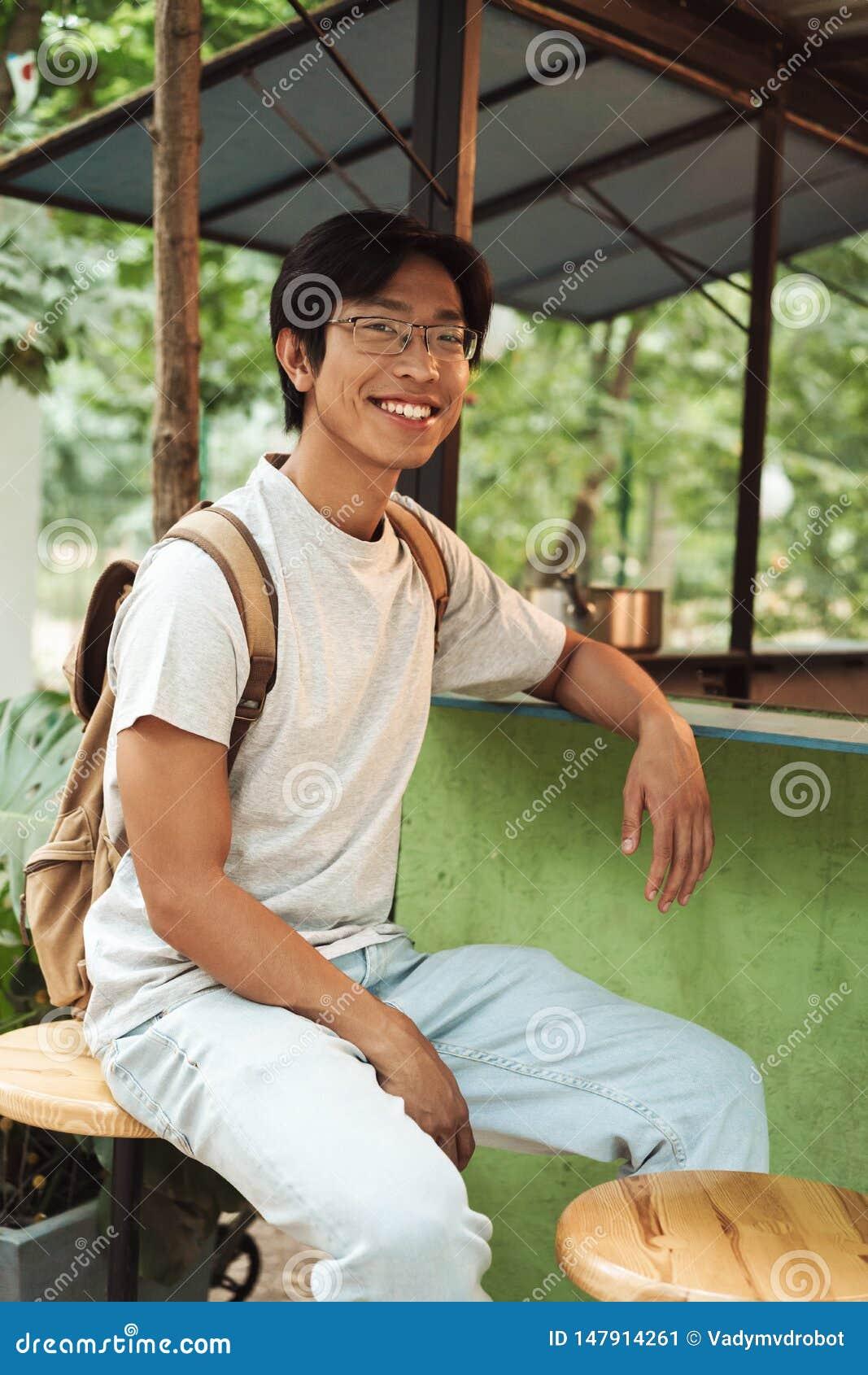 Mochila que lleva sonriente del hombre asi?tico del estudiante