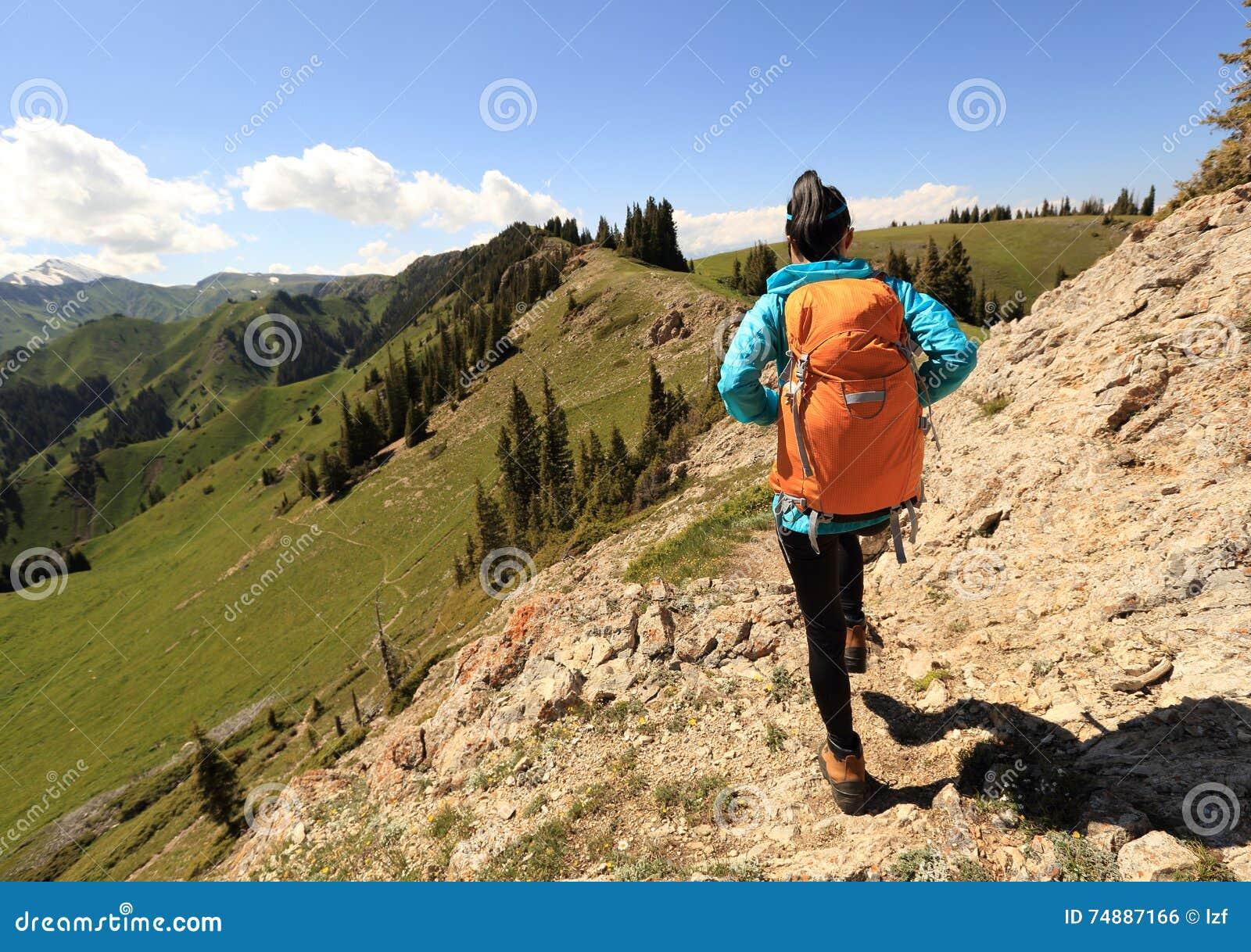 Mochileiro que caminha no pico de montanha