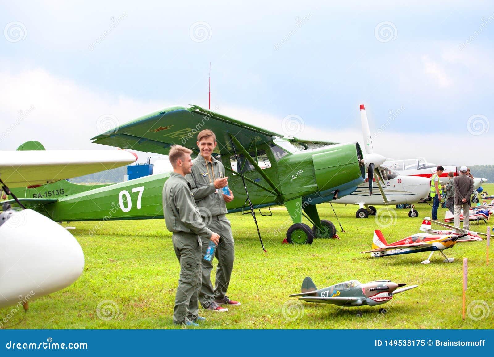 Mochishche lotnisko, lokalny pokaz lotniczy, biplanu yak 12 M i uśmiechniętych dwa młodego człowieka w pilocie odziewa na rocznik
