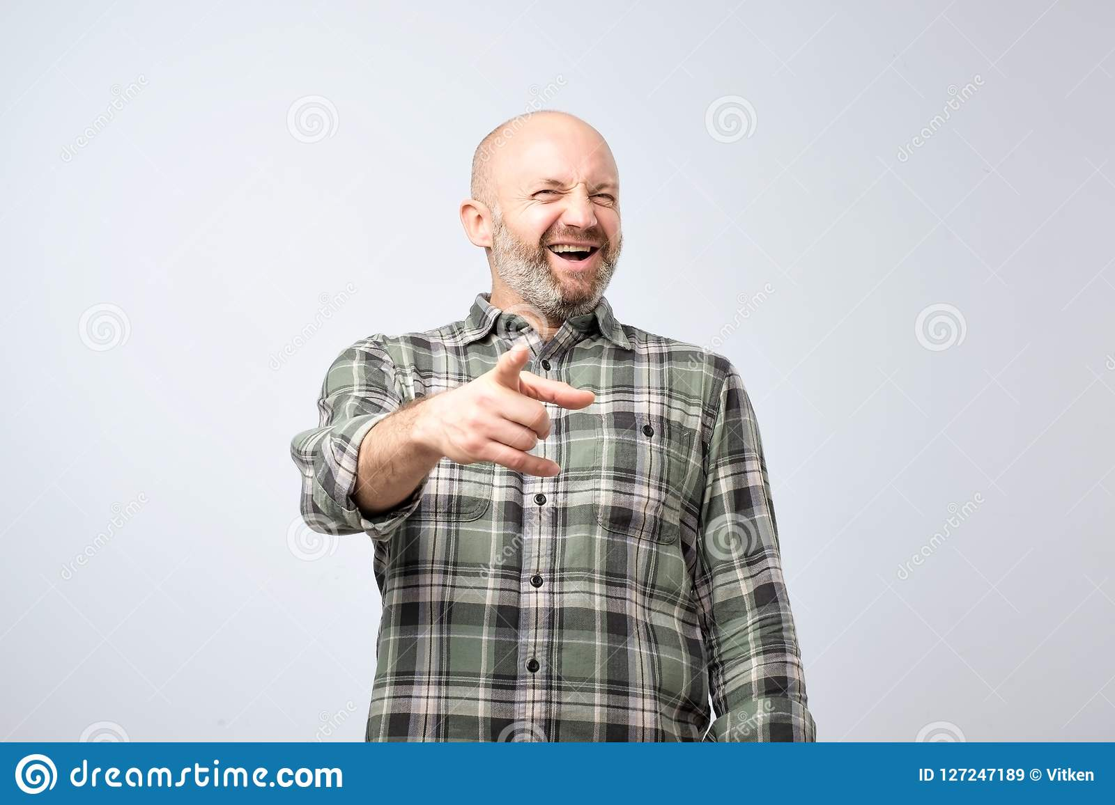 Mock or bad joke concept. Mature man pointing finger and toothy smile.