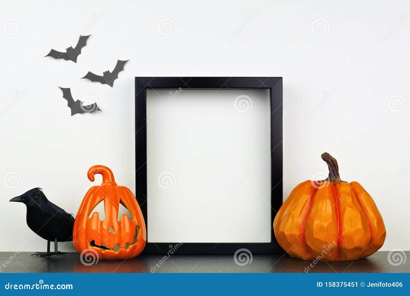 Mock up black frame with Halloween Jack o Lantern, pumpkin and crow decor on a shelf against a white wall